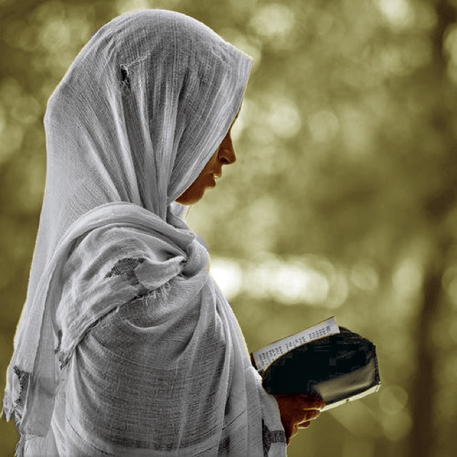Poor former Muslim woman reading Bible