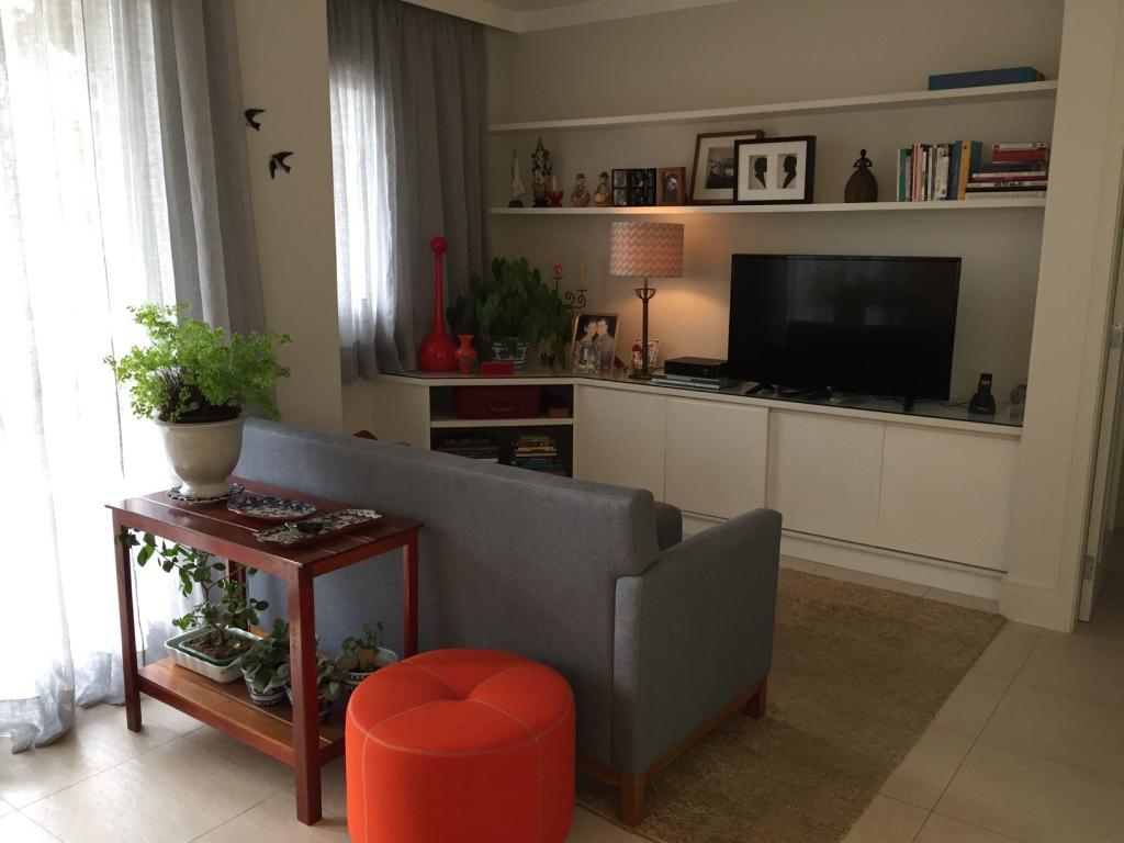 A sala de TV segue a mesma composição de elementos e o pufe laranja  ajuda a trazer as pitadas de Terra para o ambiente.
