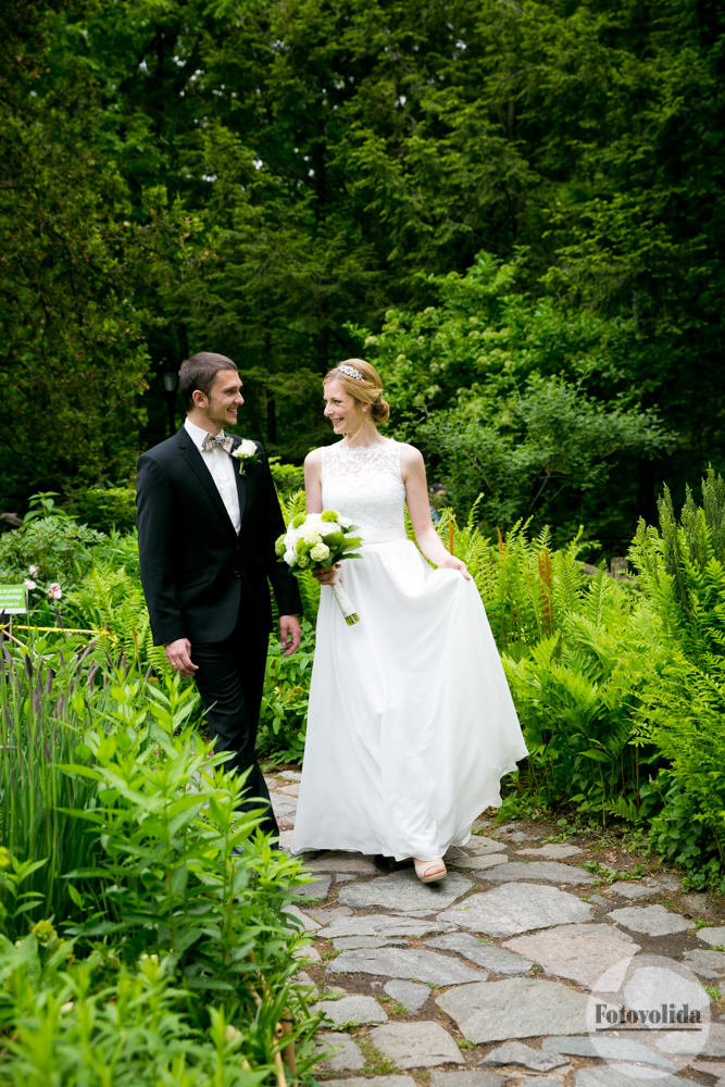 Bride and groom strolling through lush garden in Central Park