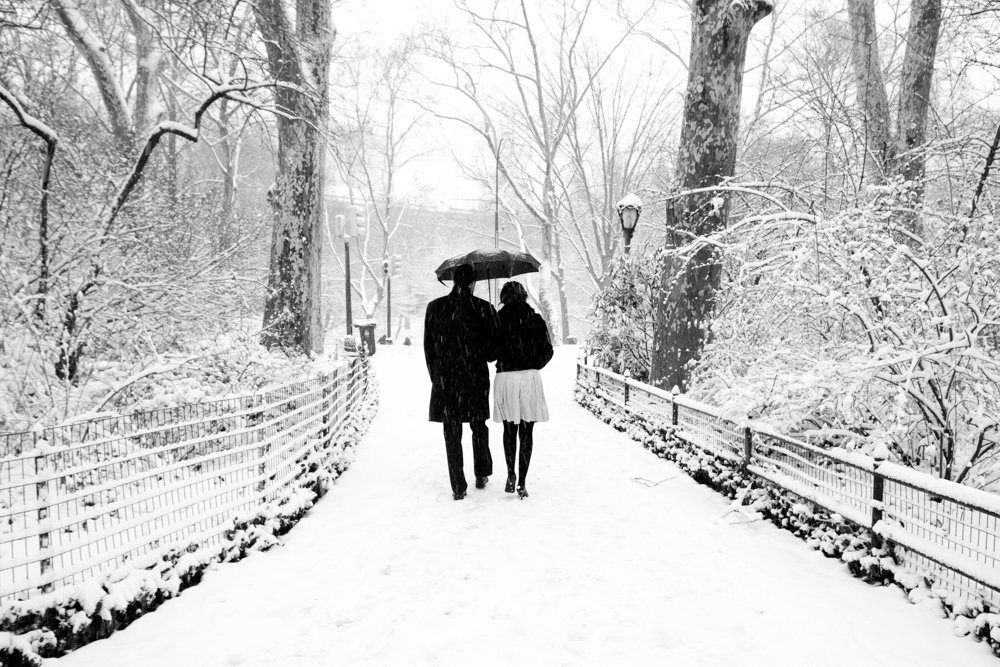 Black and white photo of couple in the snow under an umbrella in Central Park