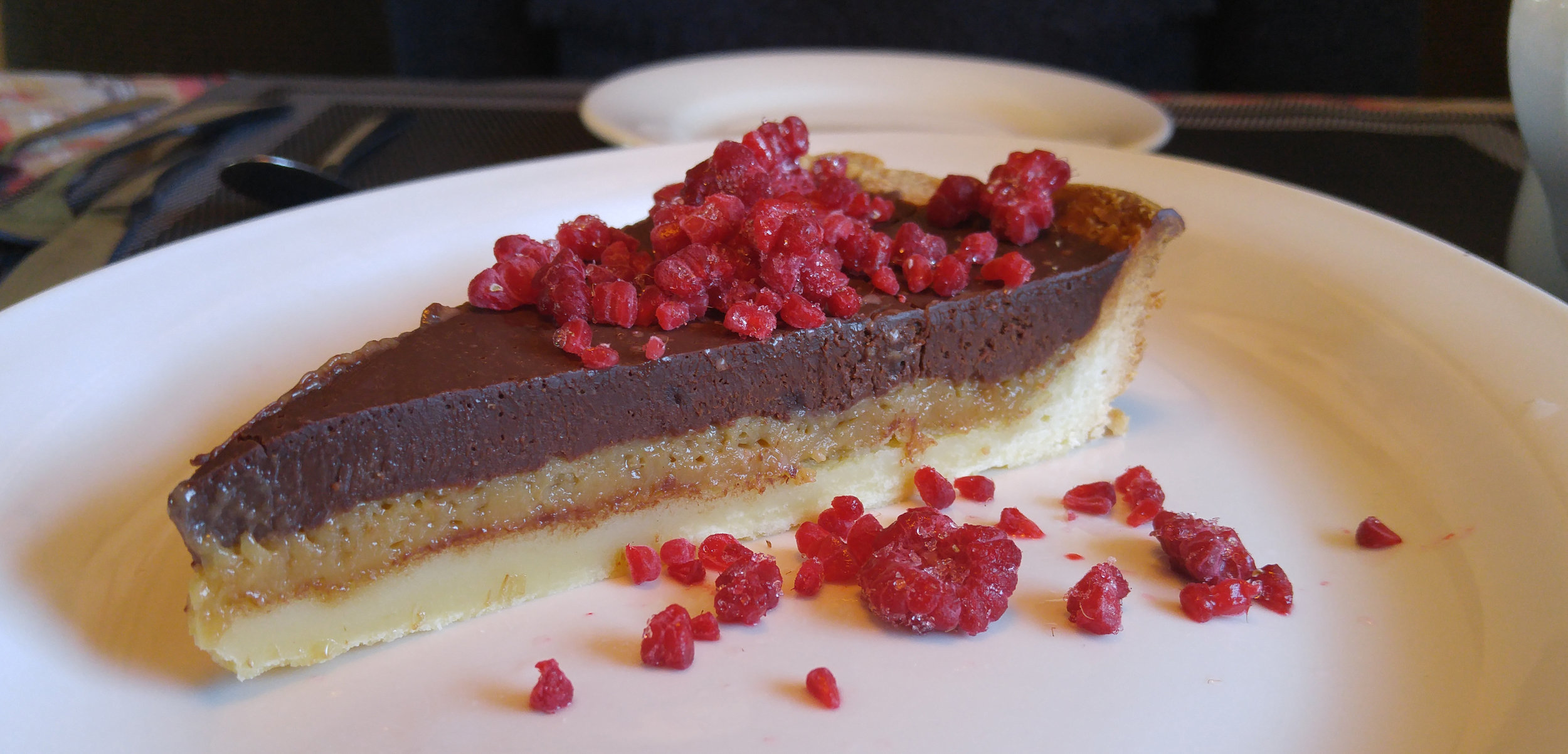 A maple tart with chocolate ganache and raspberry crumbs.