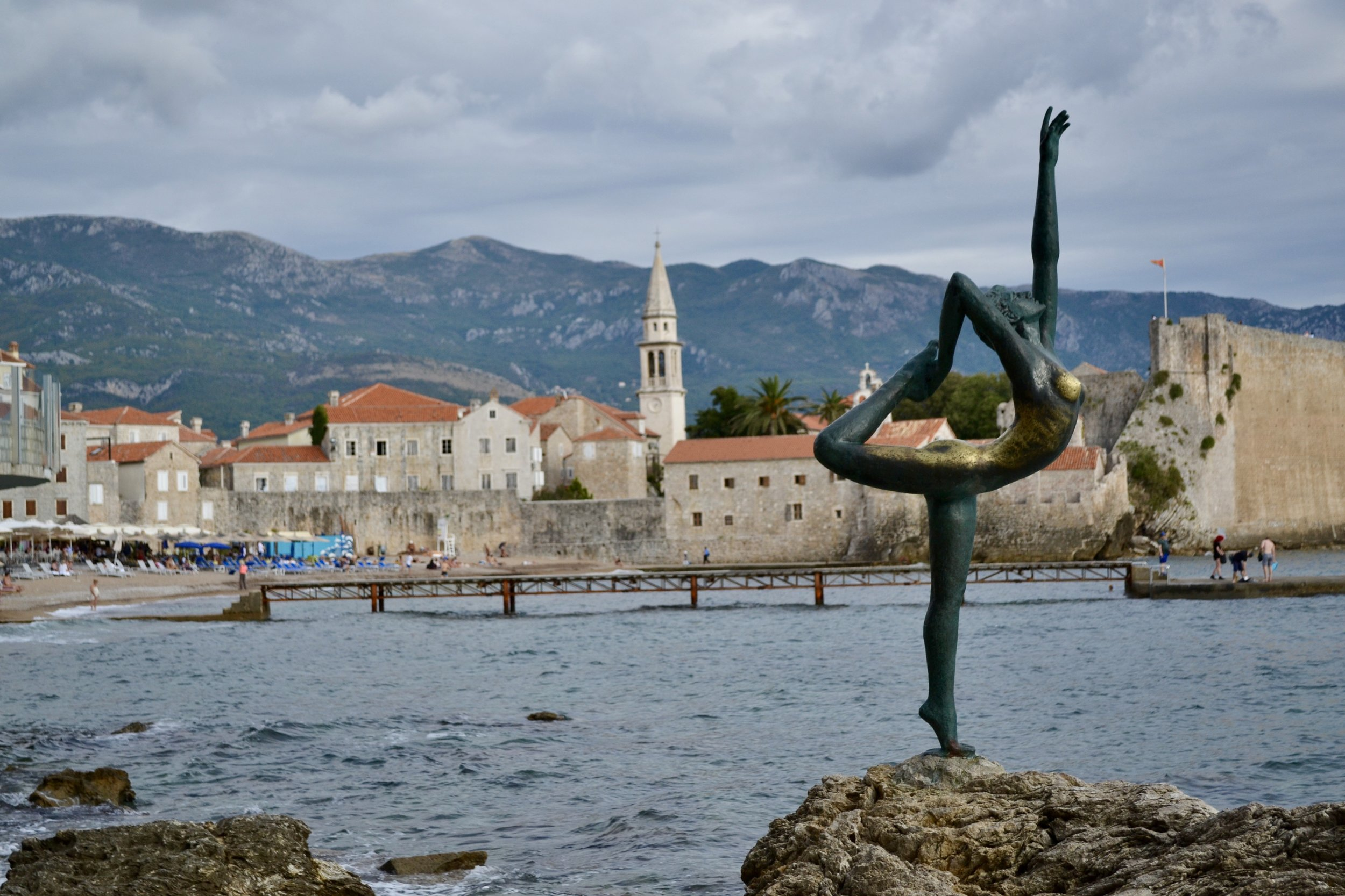 Dancing Girl statue looking on the Old Town in Budva, Montenegro