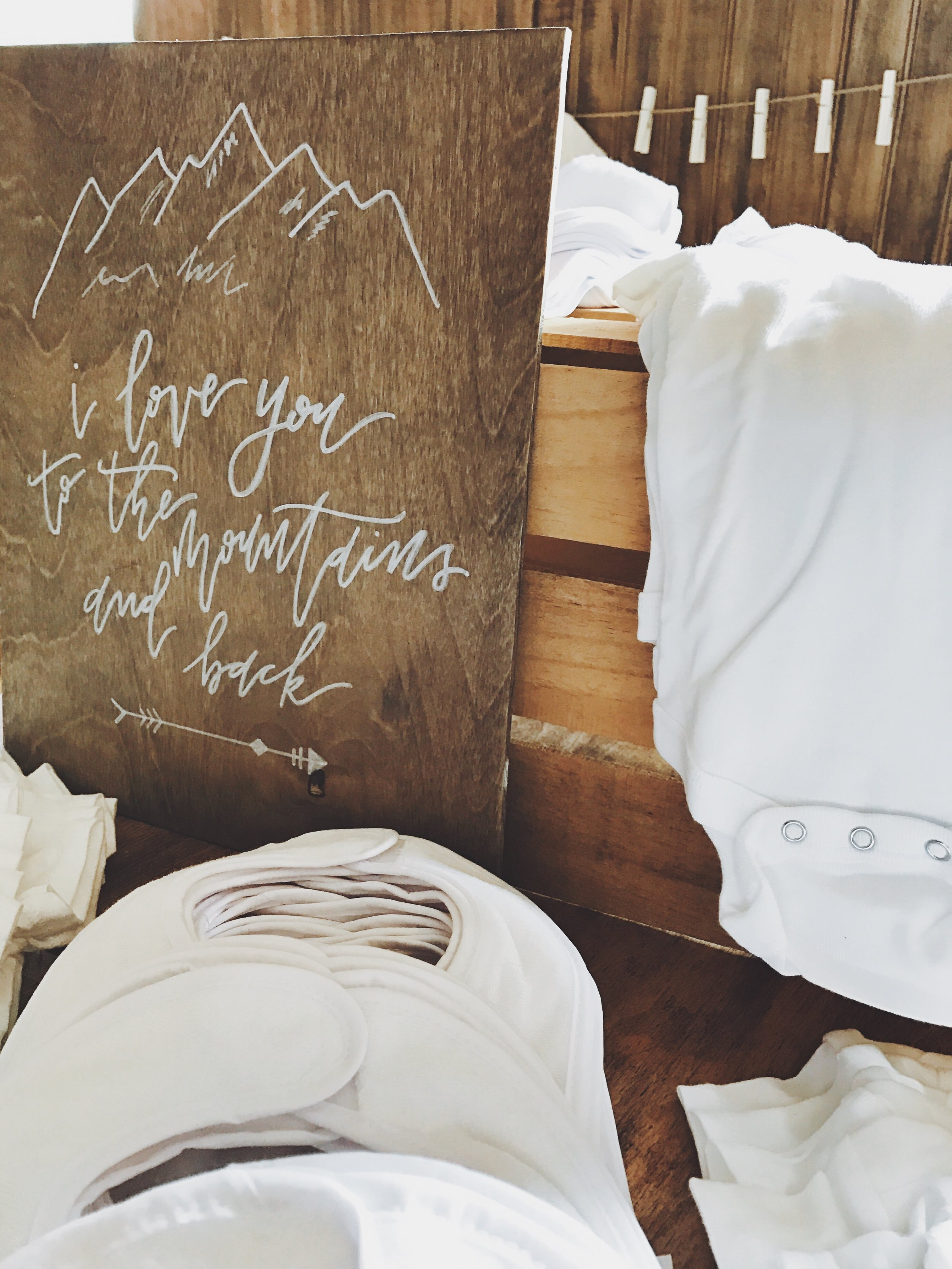 """A hand-lettered """"I love you to the mountains and back"""" Sign grazed the table where guests designed their own Baby Bibs and Onesies for the new baby."""