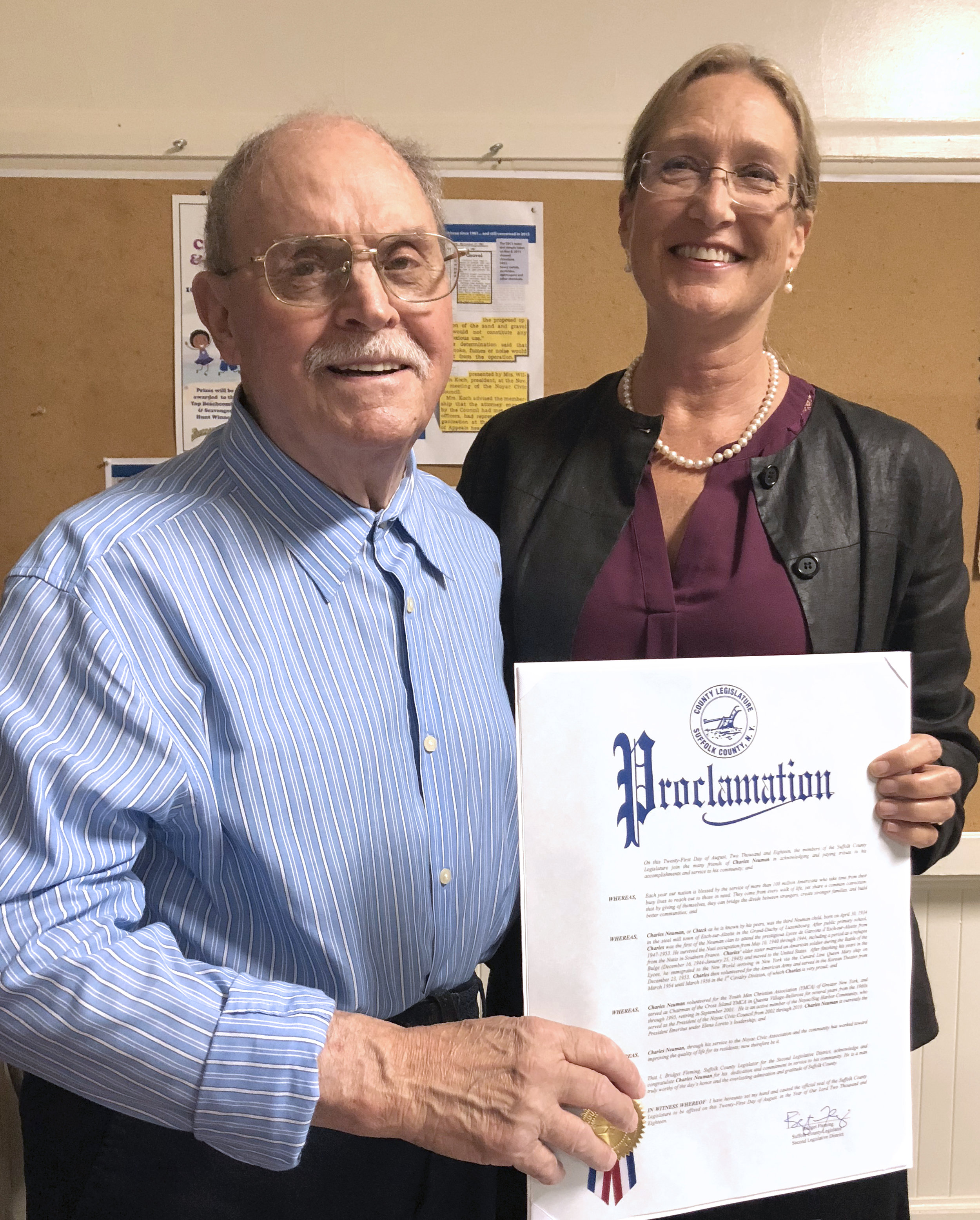 Charles Neuman receives proclamation from Legislator Bridget Flemming