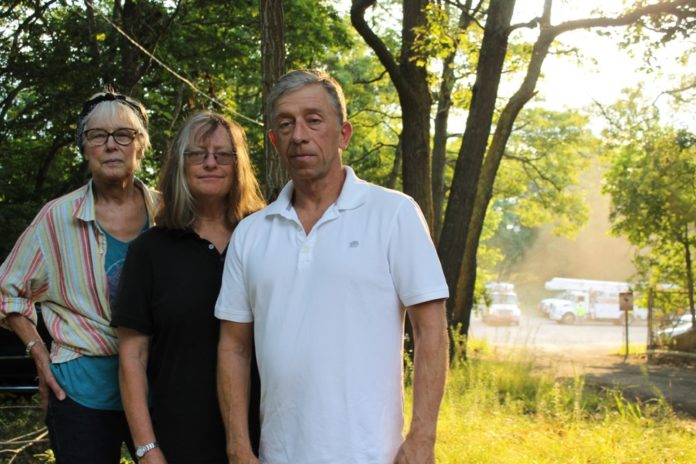 From left, Sandra Ferguson, the vice president of the Friends of the Long Pond Greenbelt, Dai Dayton, the president of the organization, and David Cummings, a board member, all oppose the village's plan to create a police vehicle impound lot on Bridgehampton-Sag Harbor Turnpike, pictured in the background. Christine Sampson photo