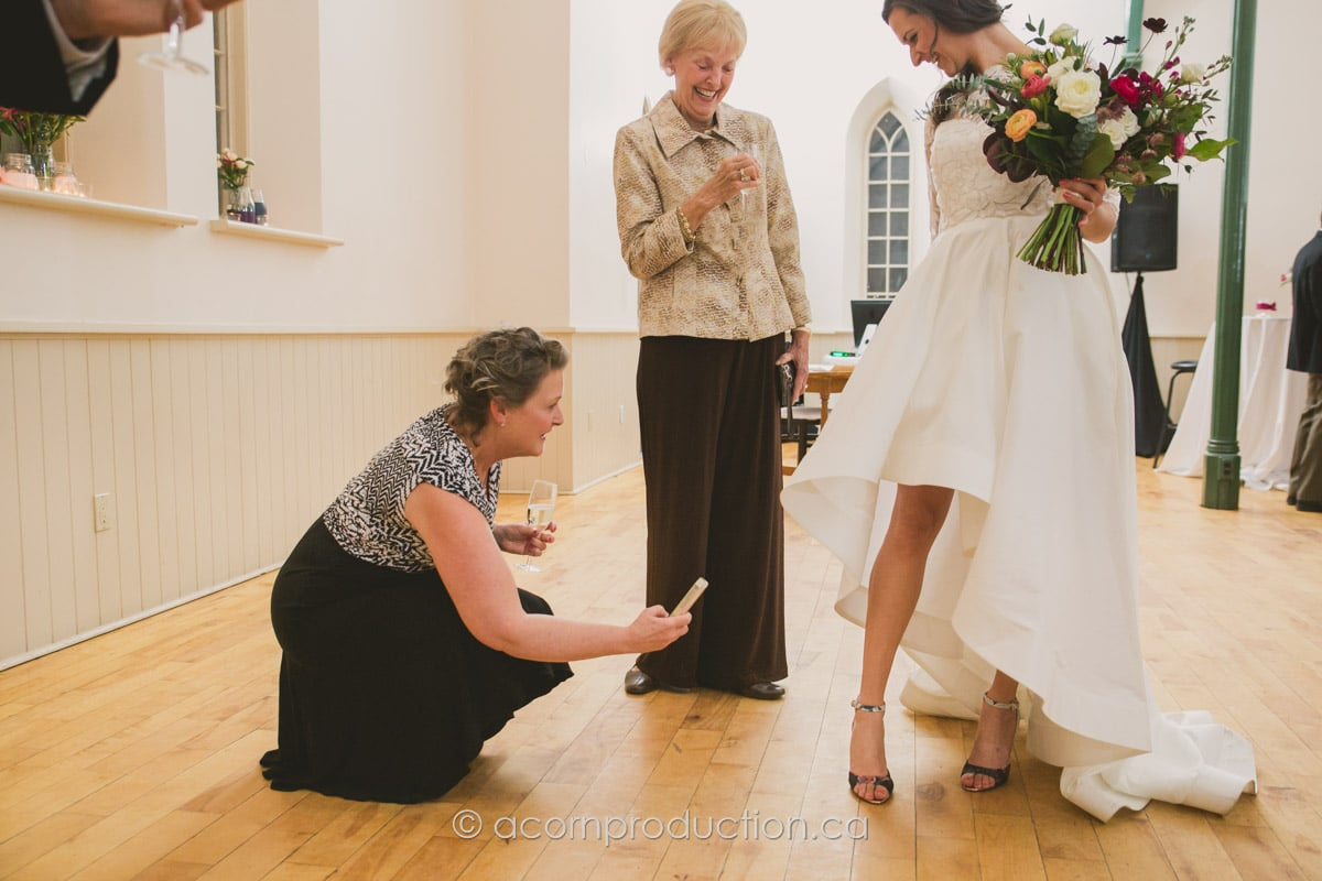 guest taking photo of brides shoes
