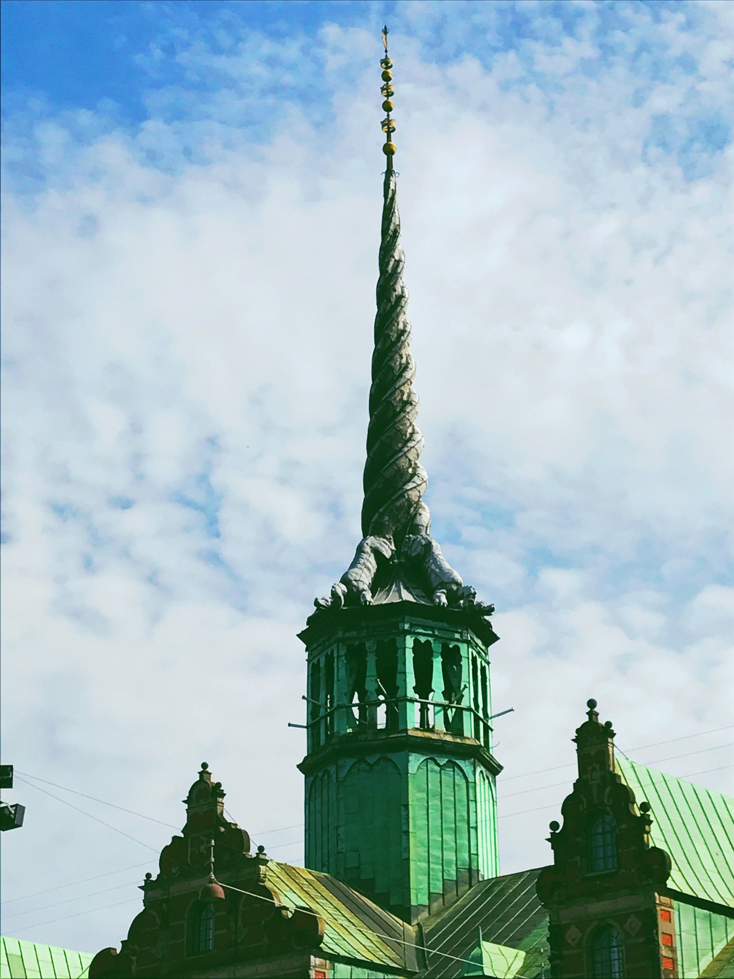 "The Old Stock Exchange. ""The four intertwined dragon tails of the dragon spire are topped by three crowns, symbolizing the Scandinavian empire (Denmark, Norway, and Sweden)."""