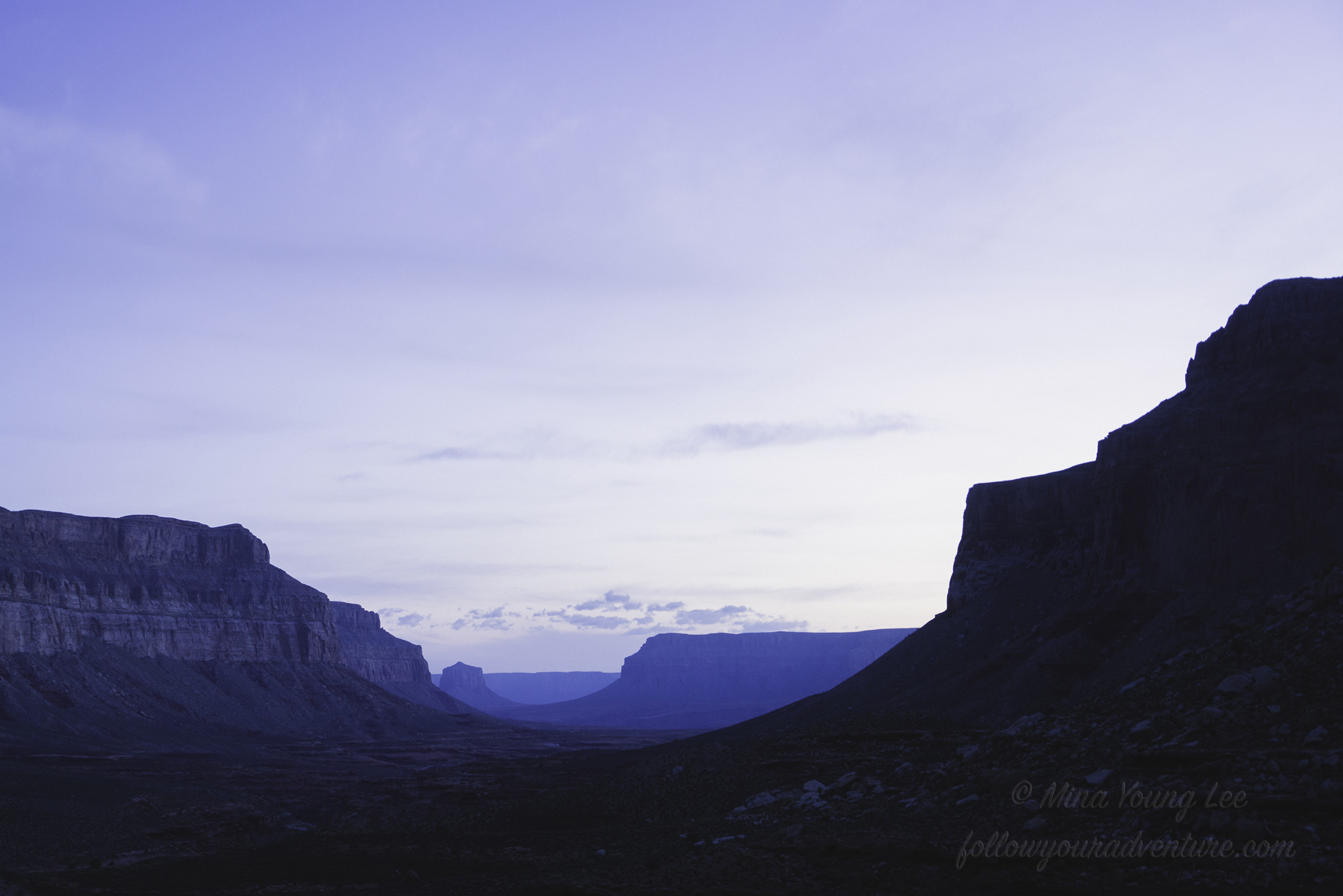 A blue glow fills the sky and canyon walls at dawn  Photograph by Mina Young Lee