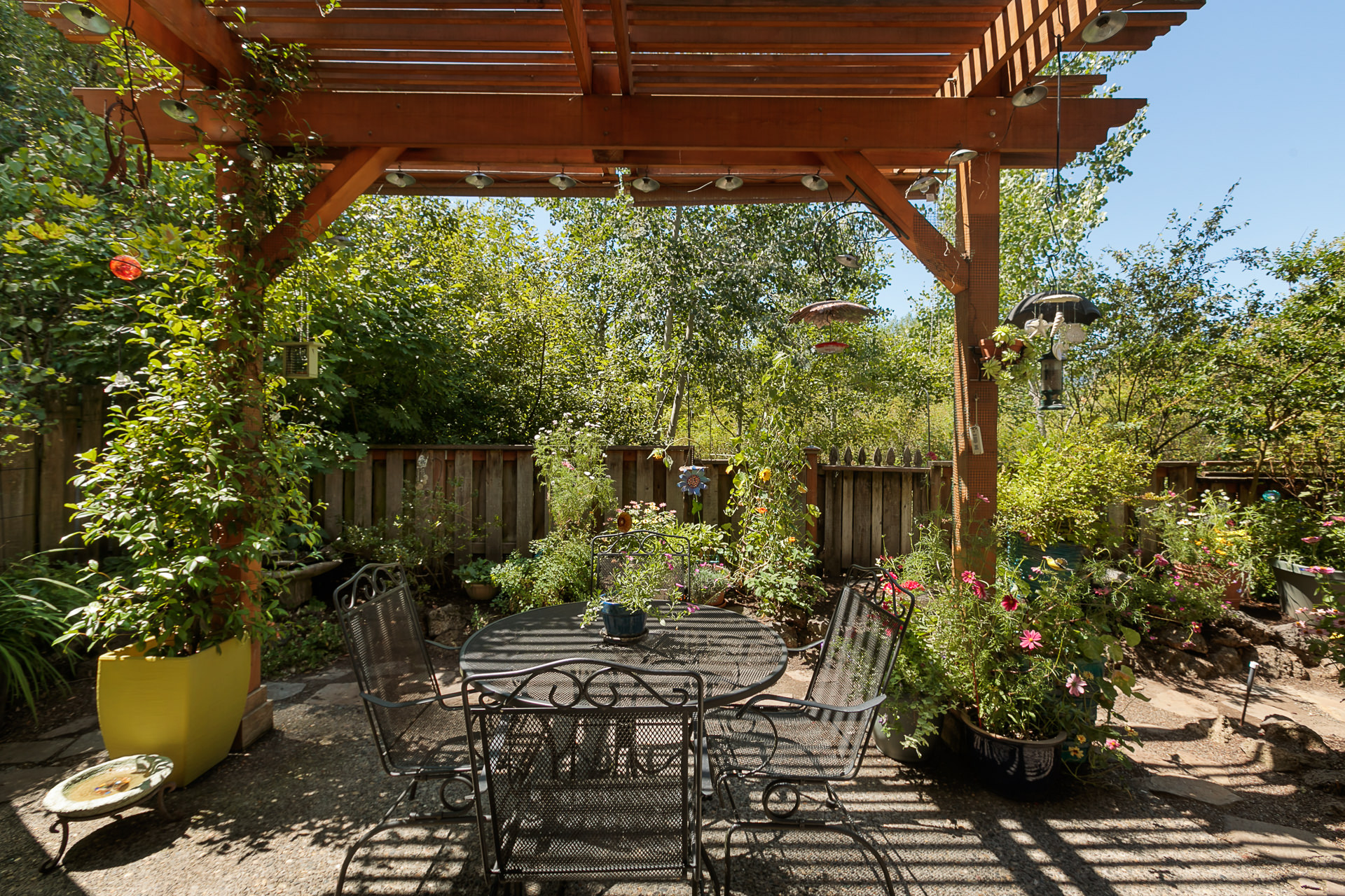 A patio with a custom built pergola, established landscaping, and private view of the nature park is a welcome retreat for humans, but the birds might enjoy it even more!