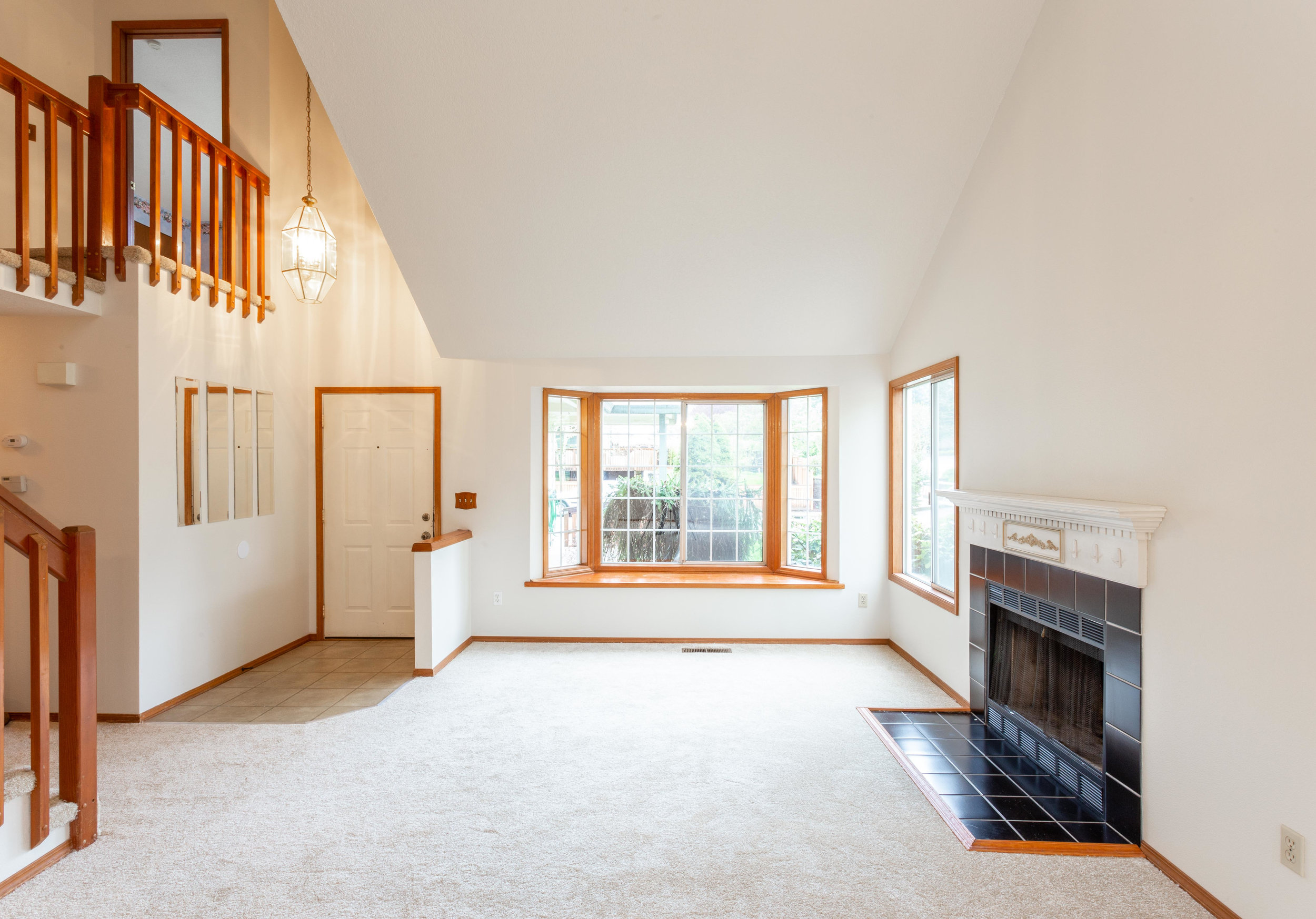 Vaulted living room with wood burning fireplace and dining room (picture taken from dining room)