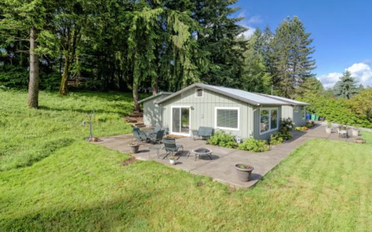 A sage green ranch hidden on top of a large sloped yard of field grass and weeds.