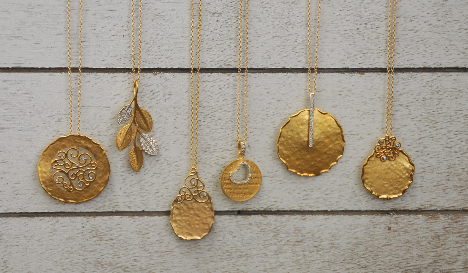 A variety of 14K yellow gold and diamond pendants by I. Reiss