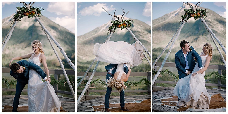 groom flips the bride, outdoor colorado wedding, natural wedding arch with florals, adventurous colorado wedding photographer, marble lodge wedding, marble colorado wedding