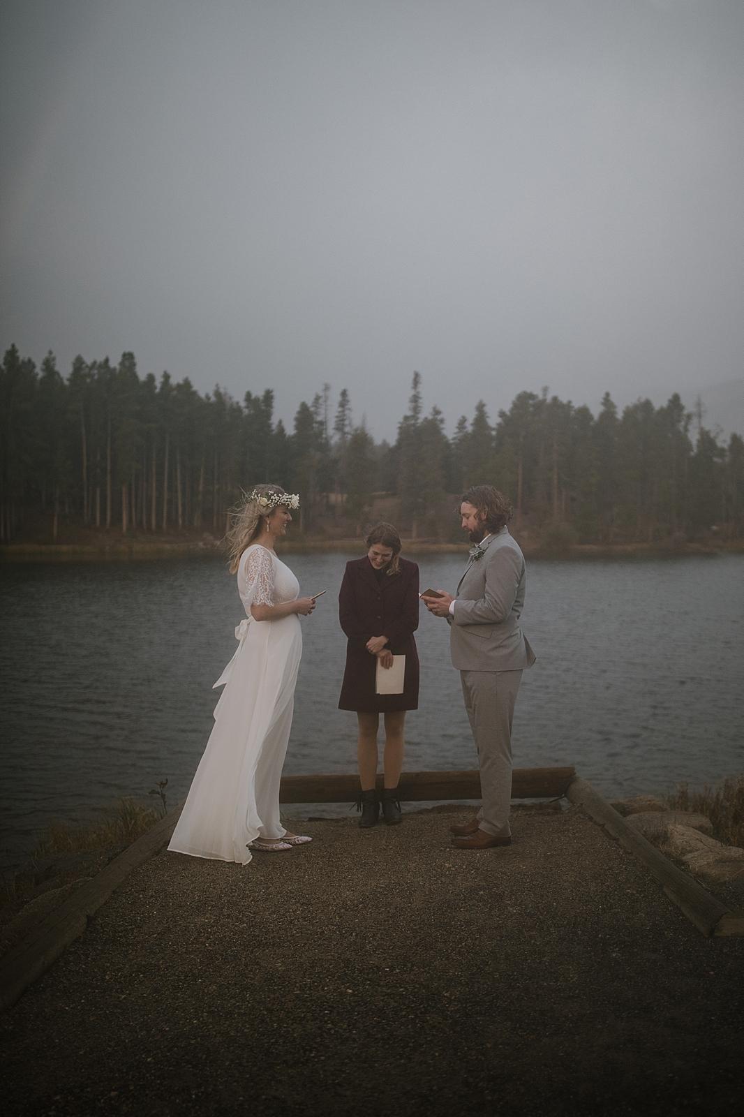 bride and groom in the rain, sprague lake dock elopement, sunrise elopement, colorado elopement, sprague lake elopement, rocky mountain national park elopement, adventurous colorado hiking elopement
