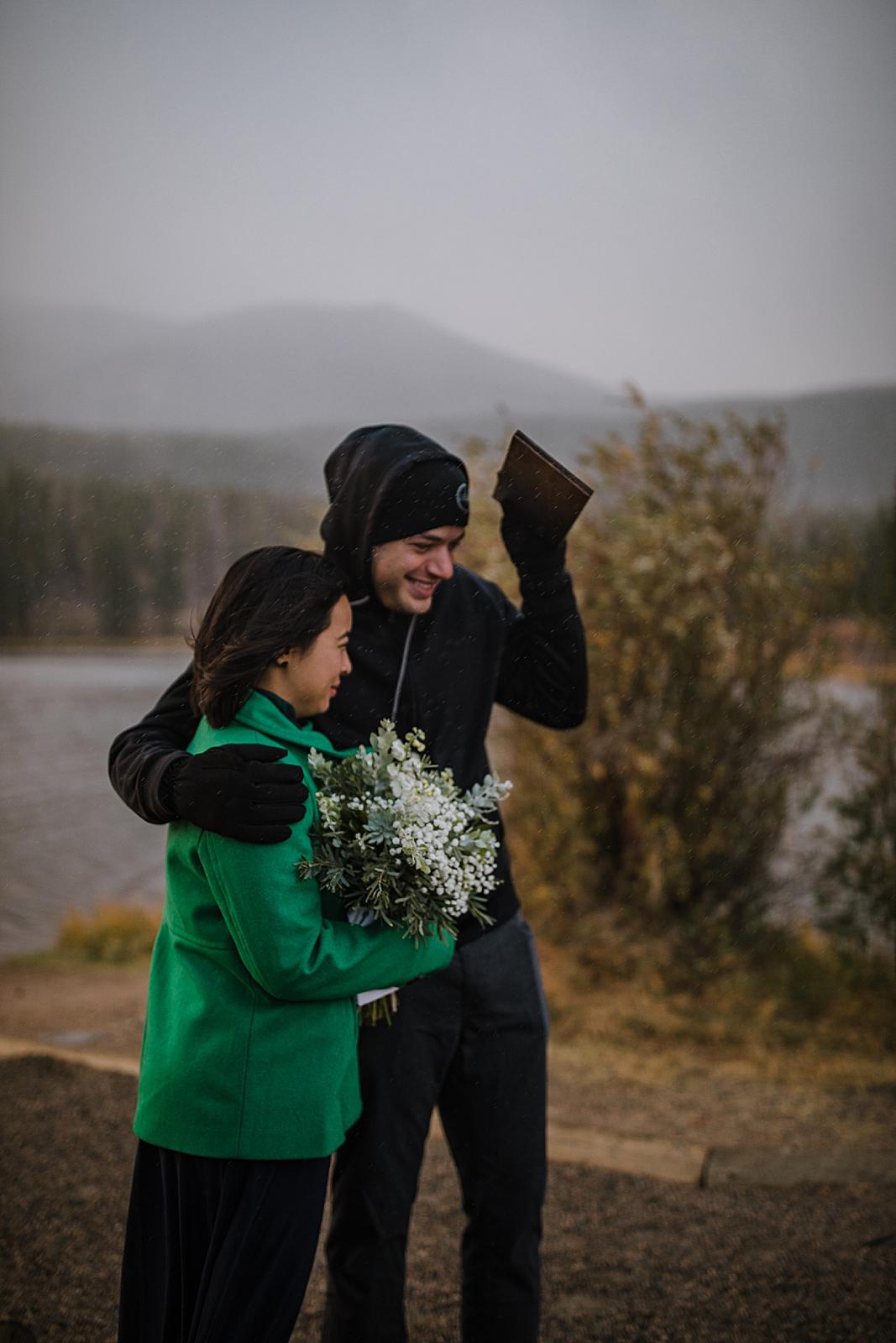 guests in the rain, sprague lake dock elopement, sunrise elopement, colorado elopement, sprague lake elopement, rocky mountain national park elopement, adventurous colorado hiking elopement
