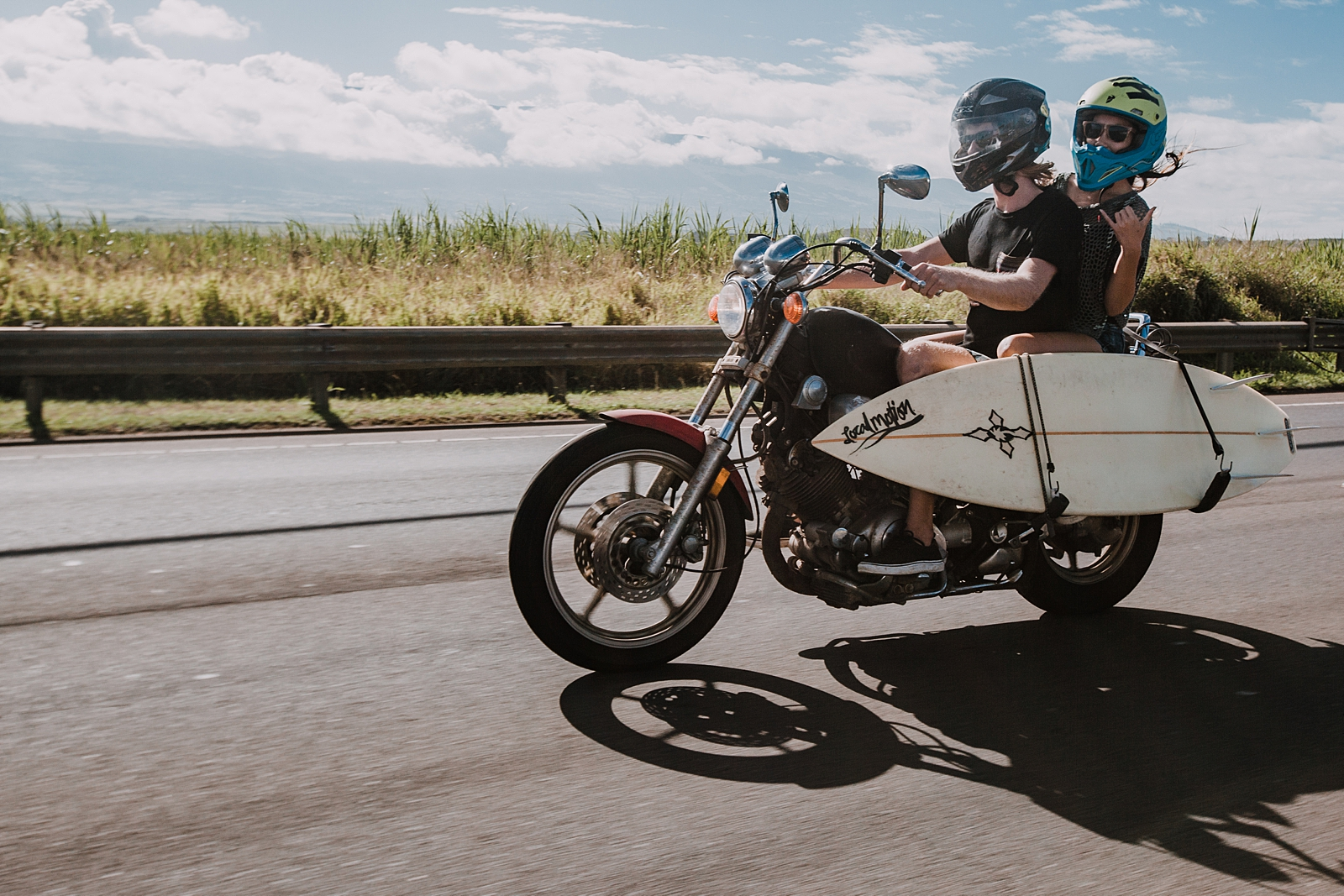 couple riding motorcycle with surfboard in maui hawaii, surfboard on a motorcyle, maui hawaii engagements, maui hawaii elopement, paia surfing, motorcycle engagements