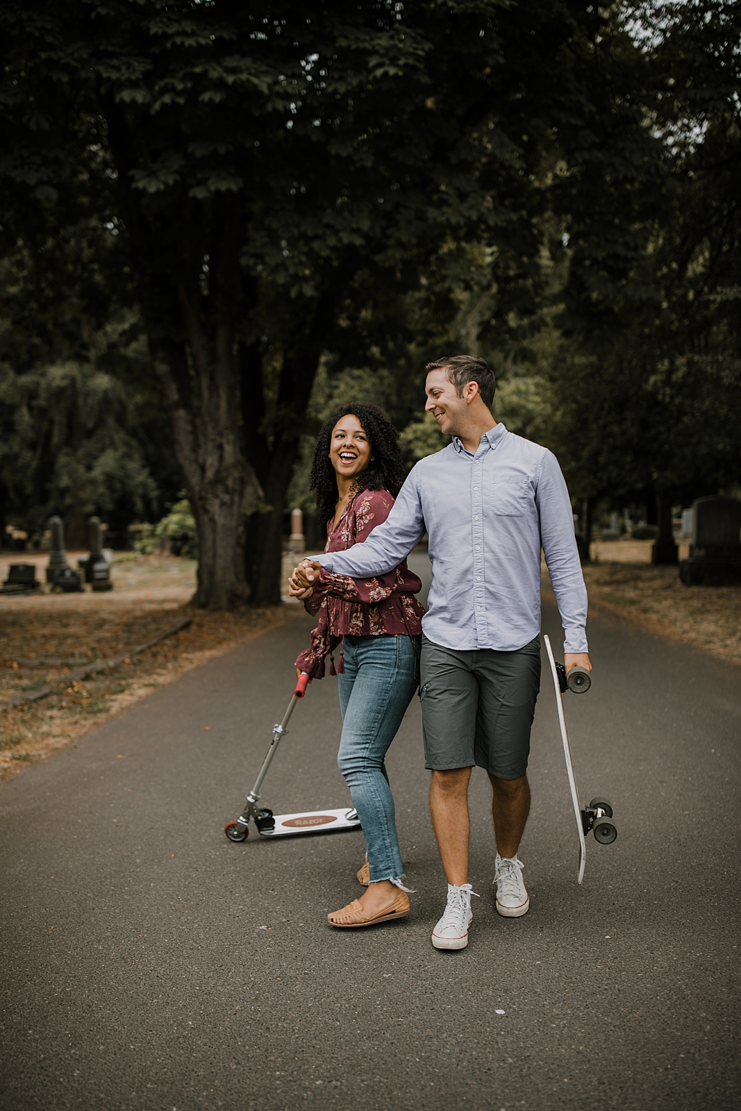 couple riding scooters in portland oregon, portland oregon engagements, portland oregon cemetery walk, riding scooters for your engagement session, downtown portland