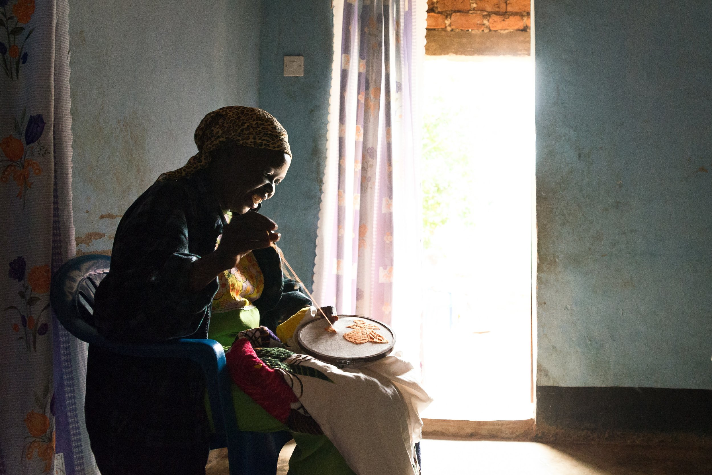 A woman embroiders a handkerchief while sharing her story of fleeing South Sudan ten years before.