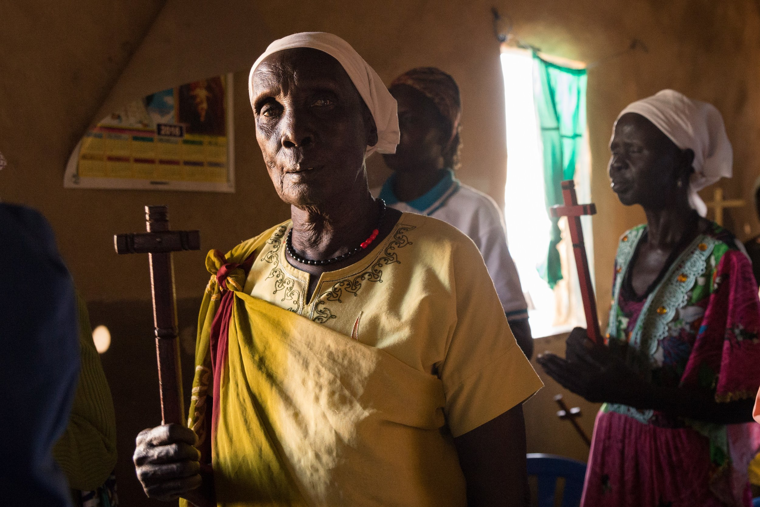 A South Sudanese refugee from the Dinka tribe holds a cross during a Protestant church service in northern Uganda.