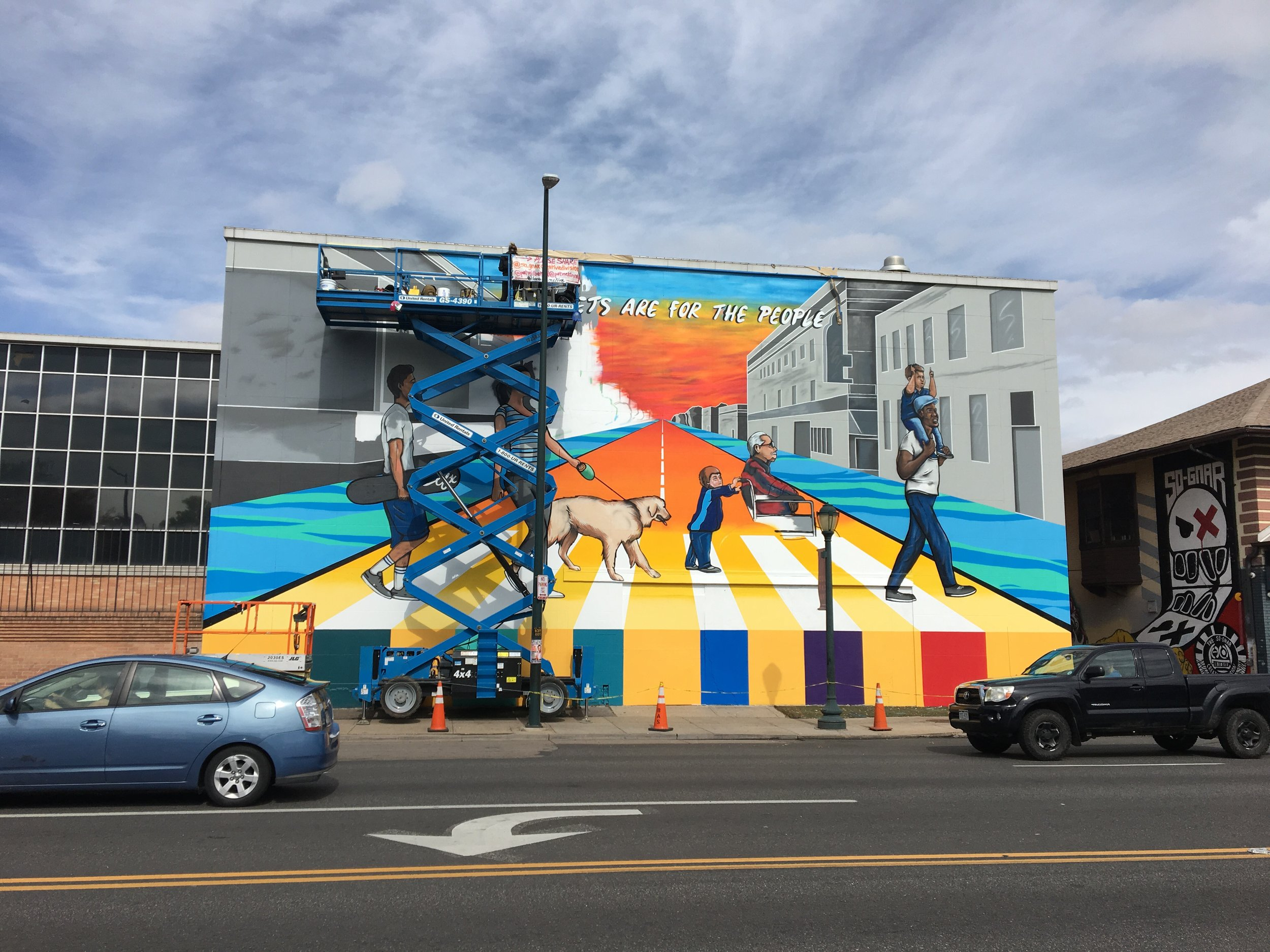 """A mural by Pat Milbery displayed in Englewood. Milbery admits his work has been criticized as being a part of city planning because he often paints large-scale murals. He says, """"Businesses, especially, believe they can't afford my art because it's so wide-spread around the city."""" (Credit: Robert Davis)"""