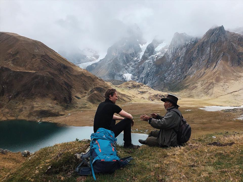 Interacting with locals with Siula Grande in distance