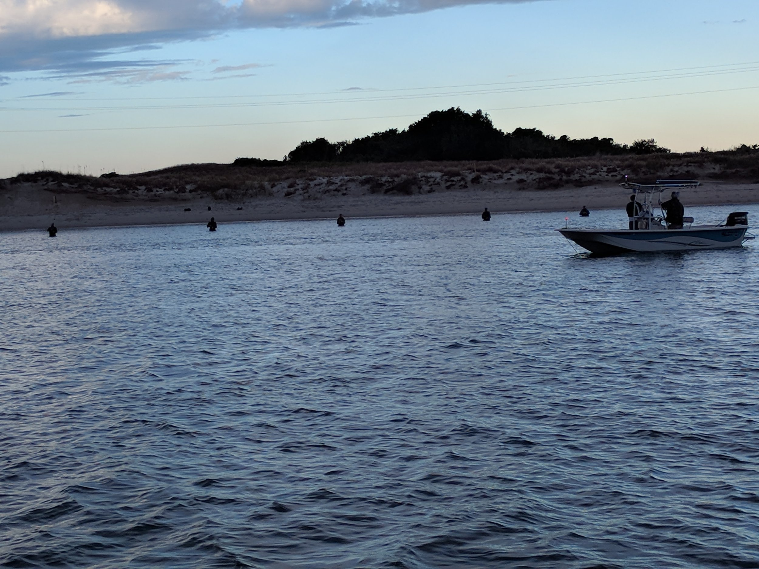 5 fisherman waist high in water.
