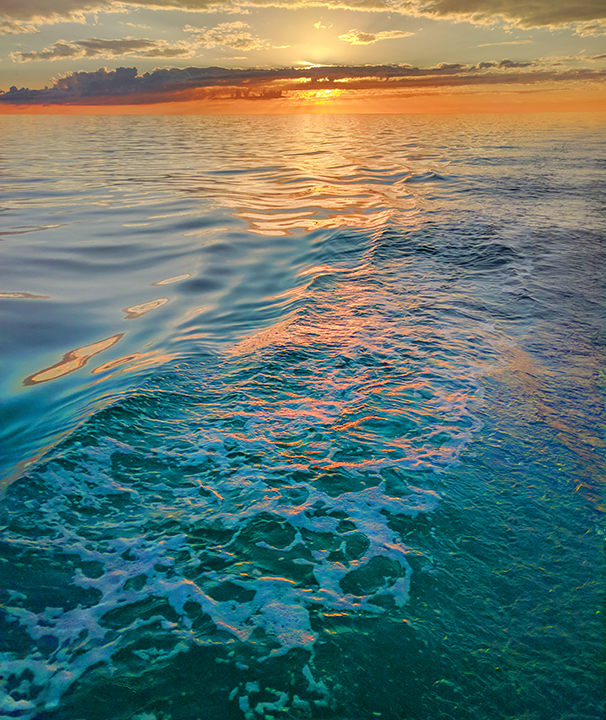 Travelling through turquoise water with a glorious sunset.