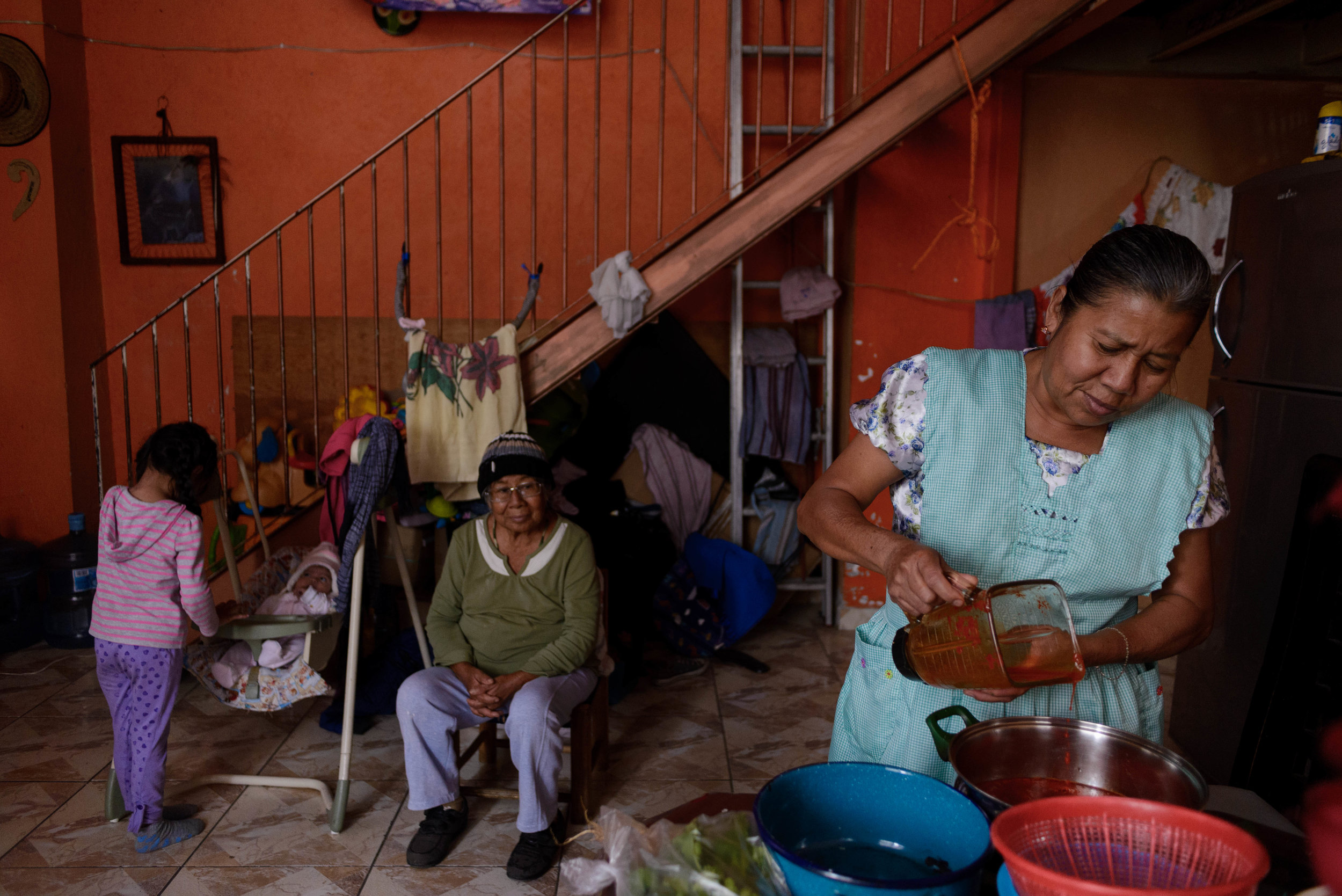 Hermenegilda prepares lunch for her family while 3 year old Merliza plays with her younger cousin and great-grandmother Agustina looks on at the scene.