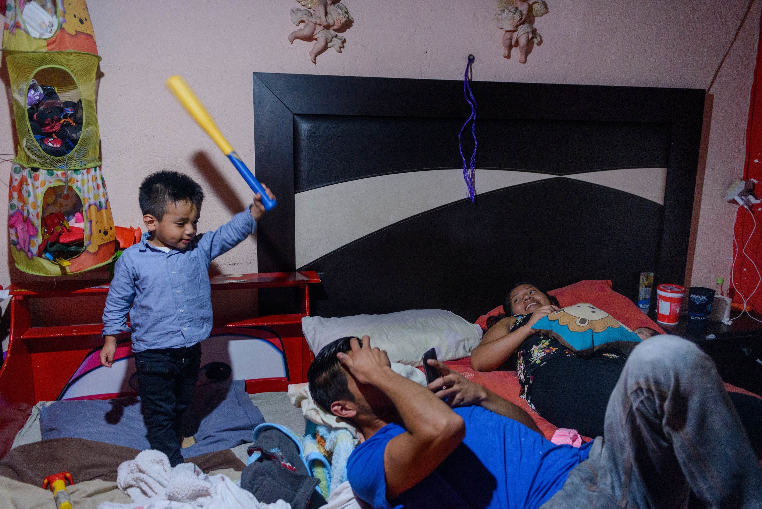 3 year old Logan threatens to hit his father with a play bat while his mother Marlen enjoys a moment of rest with her 2-month old daugher.