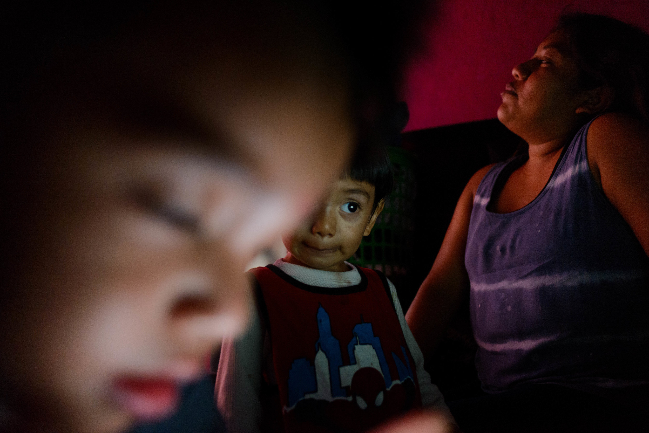 Josefina relaxes while her son and nephew entertain themselves with music videos on a laptop.