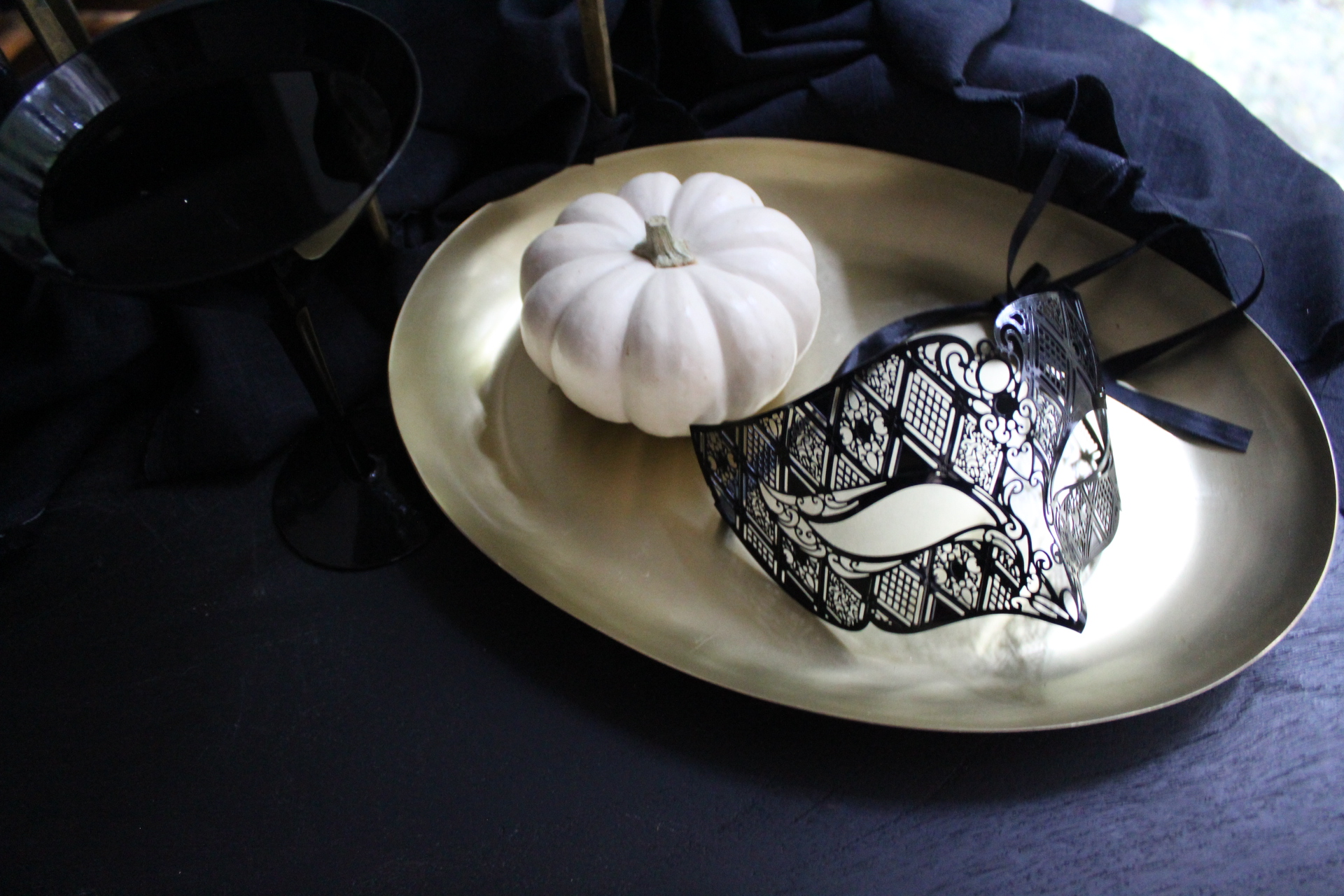 MASKED...I like to use masquerade masks as table decor scattered around for guests to try on if they are feeling naughty! Also doubles a last minute costume for anyone who arrives without!  BRASS...I love this brass candelabra from Crate & Barrel. It allows you to drape the linen or fill with pumpkins or flowers so easily. Bonus:it's on super sale right now for only $24.95! Looks great with or without tapers in it.