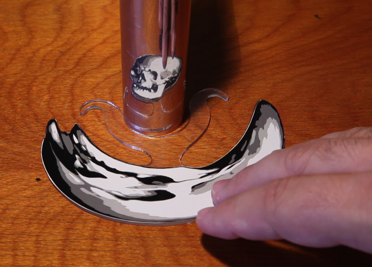 Memento Mori (Catoptric)  uses a pre-cut printed distorted image made in varying diameters to fit different pipe sizes
