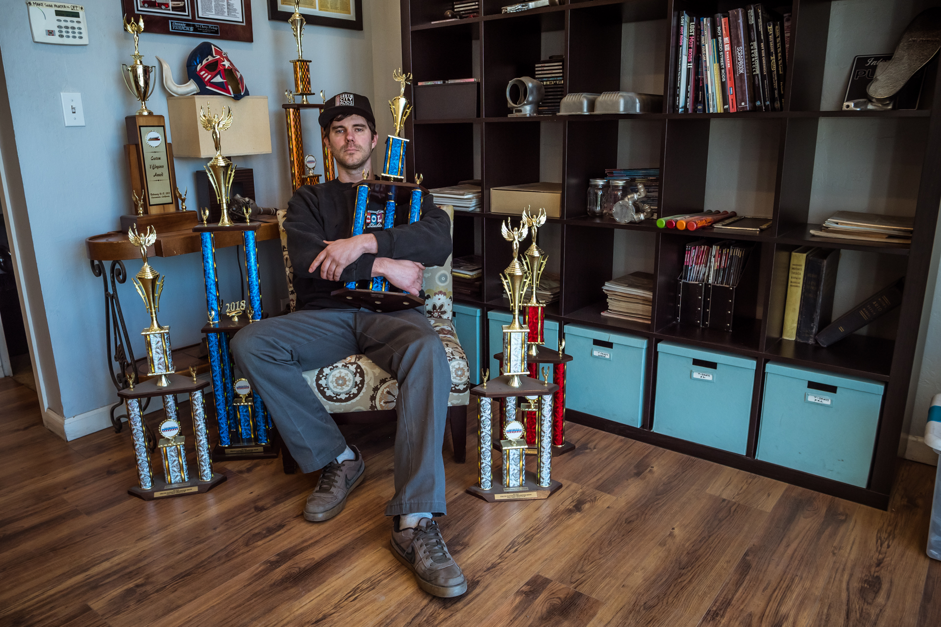 Bill Sitting Among a small portion of the trophies he's won in his life for excellence to the highest degree.
