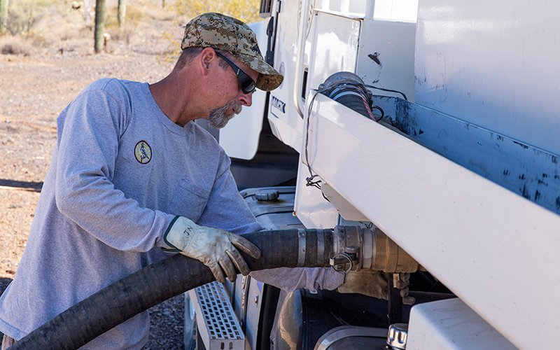 Jed Nitso, a heavy equipment operator with Arizona Game & Fish Department, empties a truckload of water into a catchment near Lake Pleasant. An avid outdoorsman, he has worked for the department for 14 years. (Photo by Nick Serpa/Cronkite News)