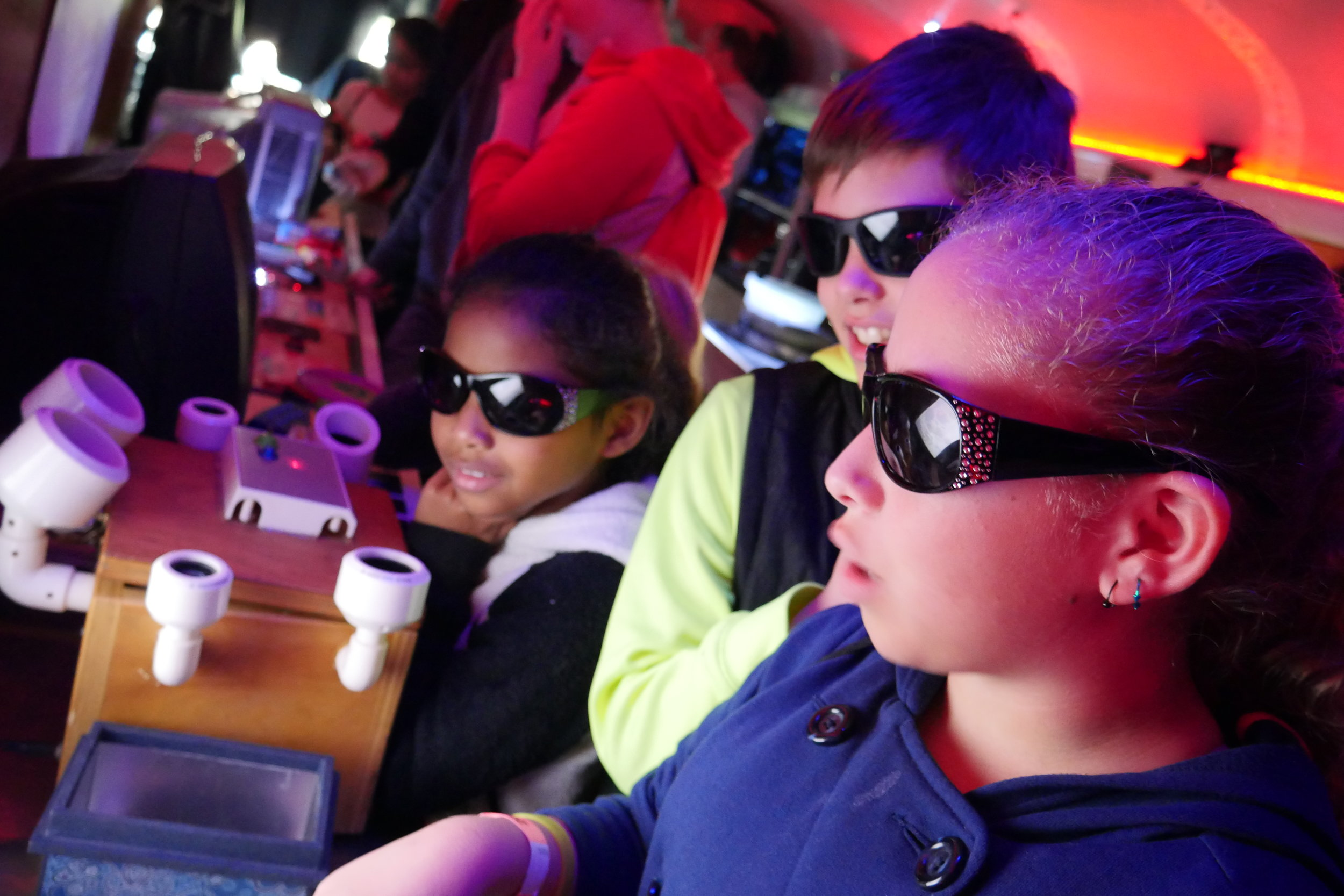 Inside the Physics Bus, a group of children put on special glasses and watch a movie through a warped television display. (Nicholas Serpa/DD)