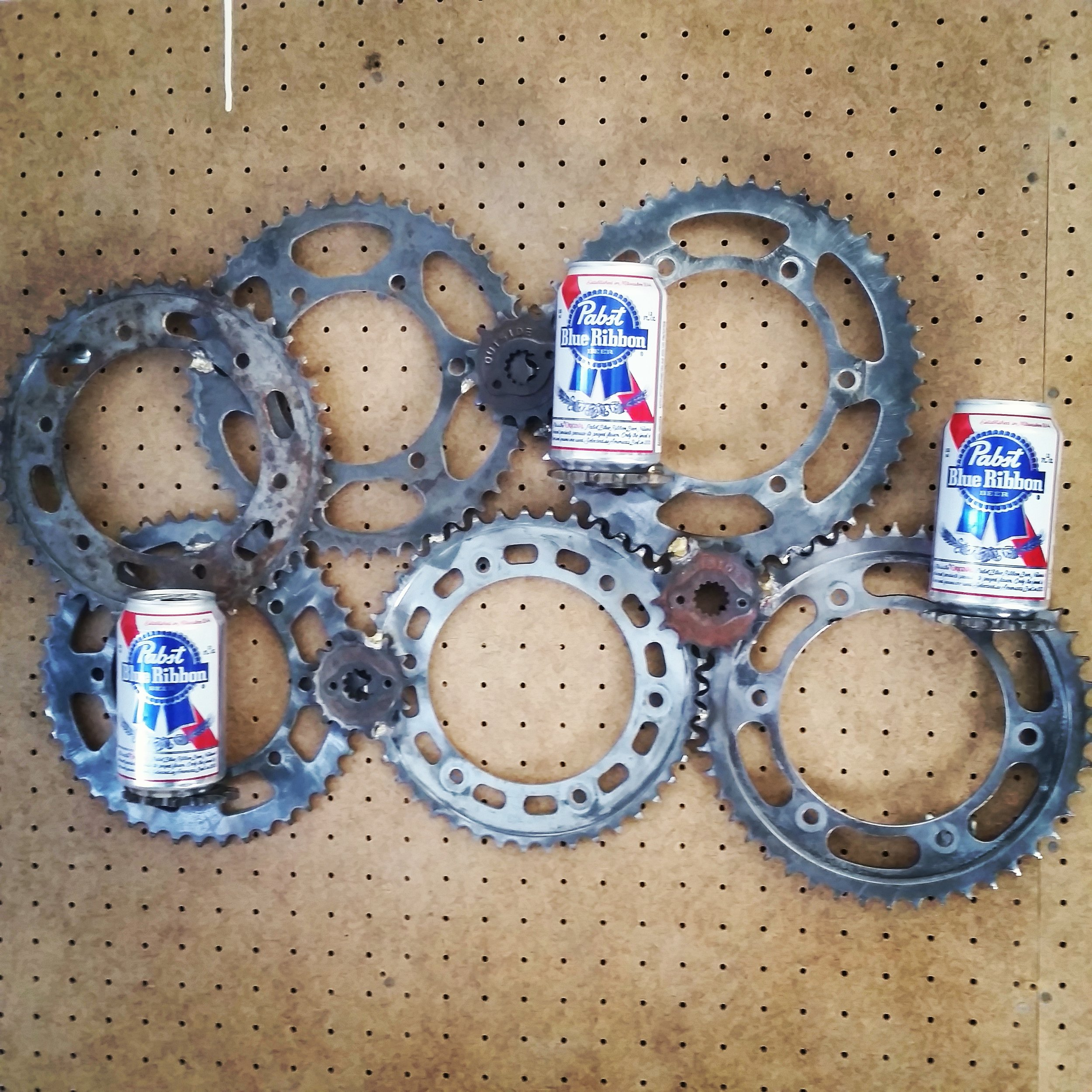 A piece of wall art made from old motorcycle sprockets brazed together.