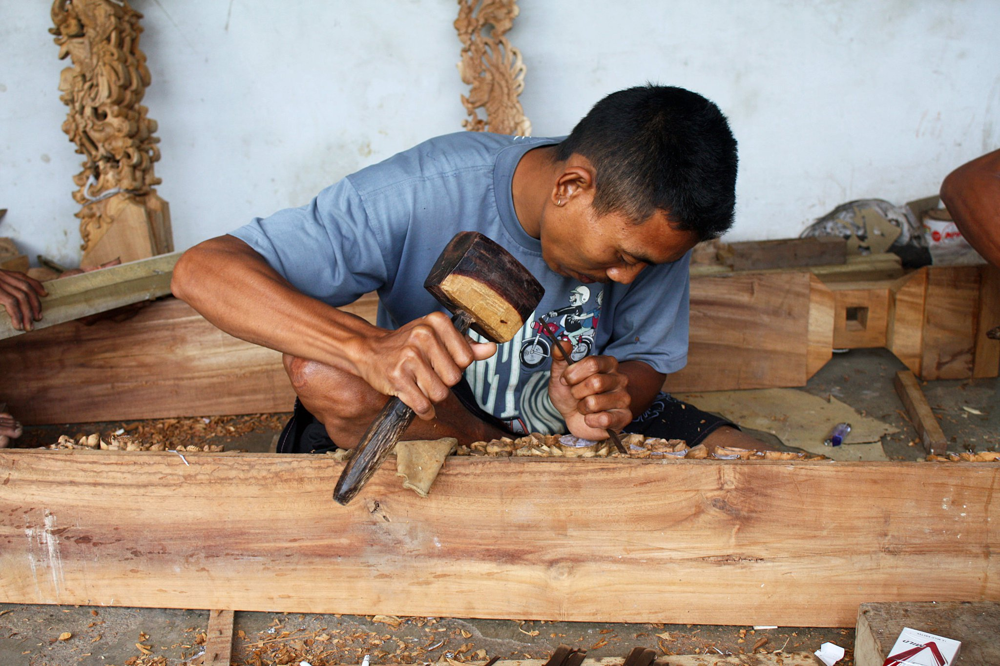 You can see how intricate the finished pieces are behind this wood worker