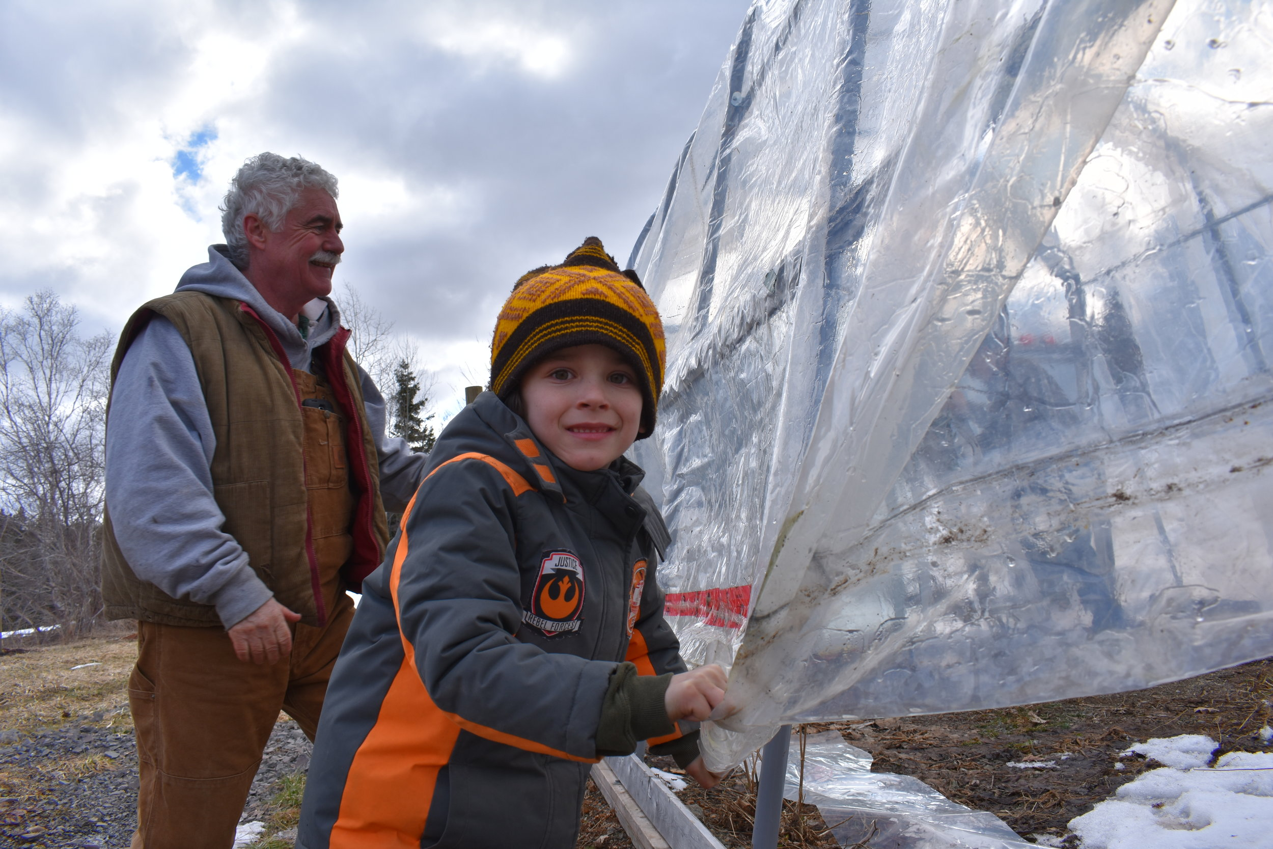 Young Jimtown Dept of Public Works superintendent Lee Robin Braid helps wrap the greenhouse under the Mayor's supervision.