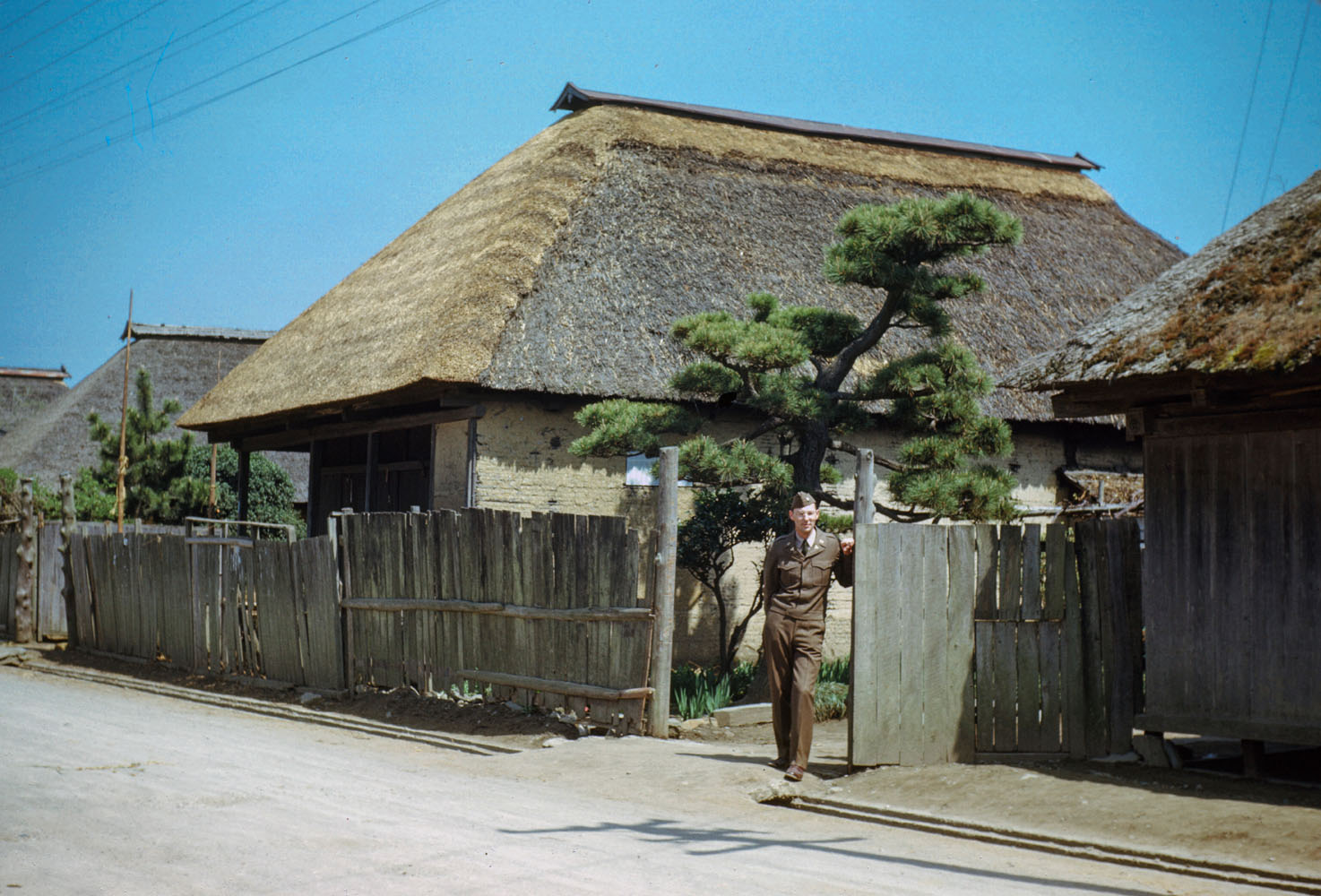 204- George Butler in front of village house