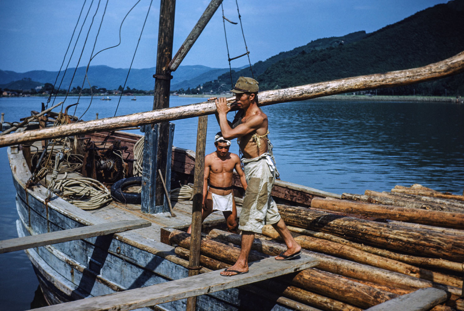 409-Man Unloading timber from boat, Location?