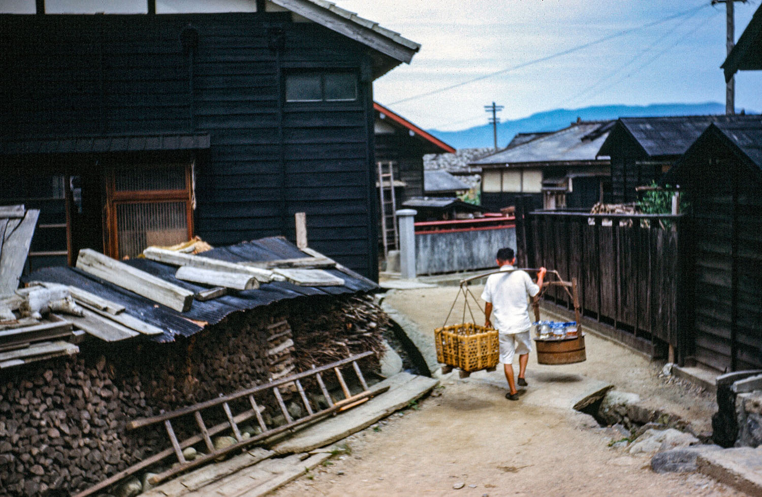 492- Man with Baskets Walking through village