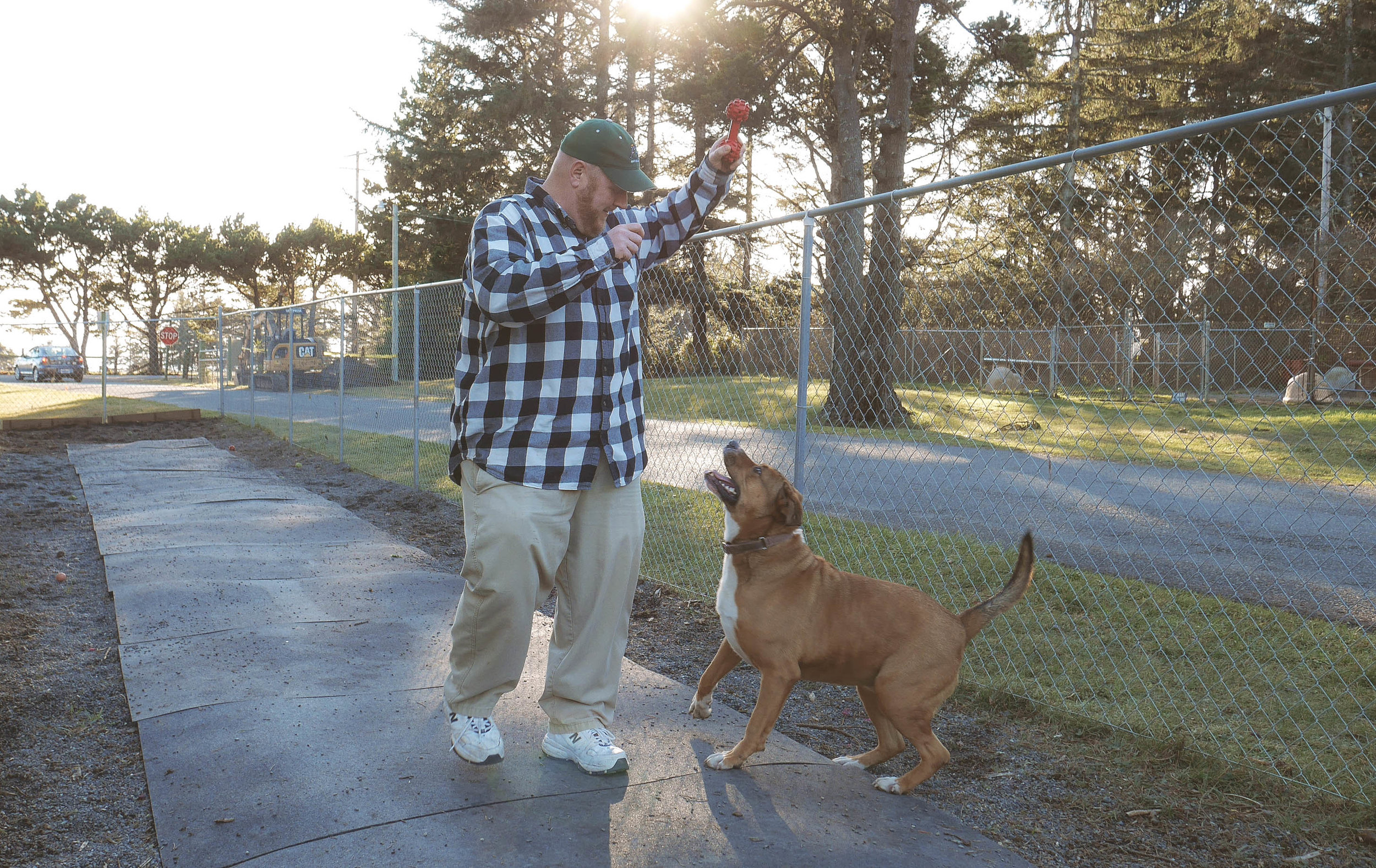 Justin Riggs, Del Norte Animal Control Shelter Manager, plays with Mandy in the dog run made possible by community donations and volunteers.