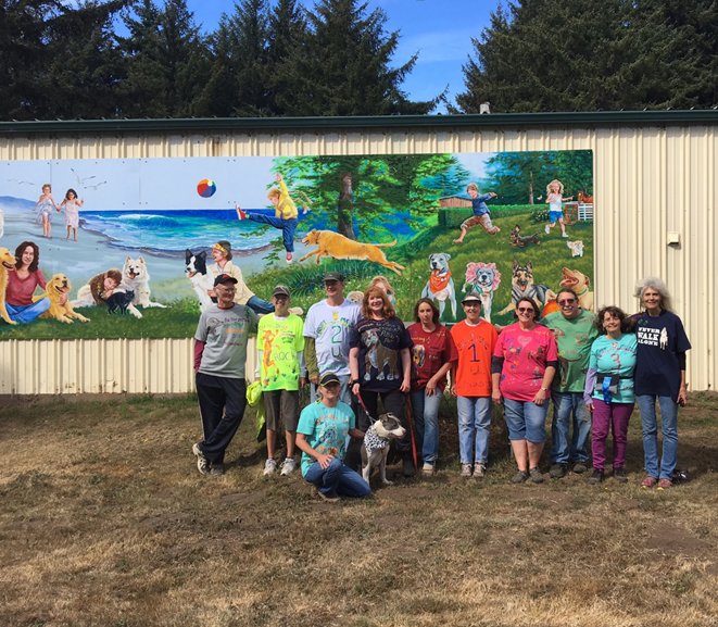 Many of the shelter's regular volunteers pose in front of a beautiful mural added to the side of their kennel building in 2015. The mural was paid for by donations and honors the volunteers and some of the dogs that have been adopted from the shelter.