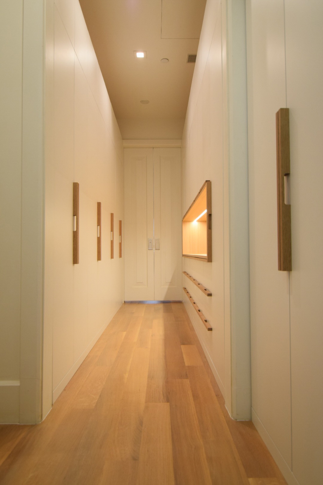 custom-walk-in-closet-white-lacquer-finish-maple-interior-white-oak-handles-white-oak-accent-open-display-cabinet-portrait-view.jpg