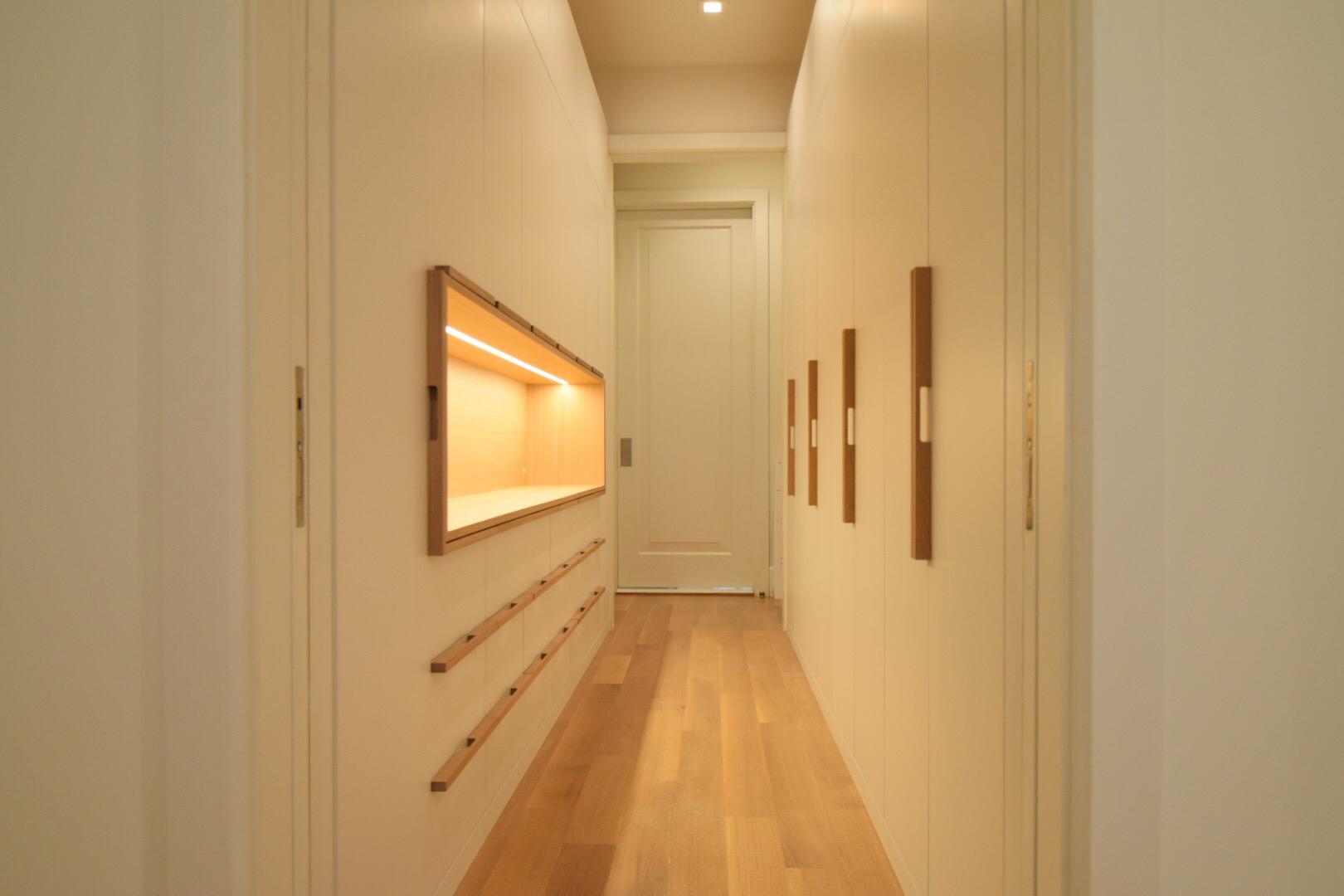 custom-walk-in-closet-white-lacquer-finish-maple-interior-white-oak-handles-with-drawers-and-white-oak-accent-open-display-cabinet-with-LED-lighting.jpg