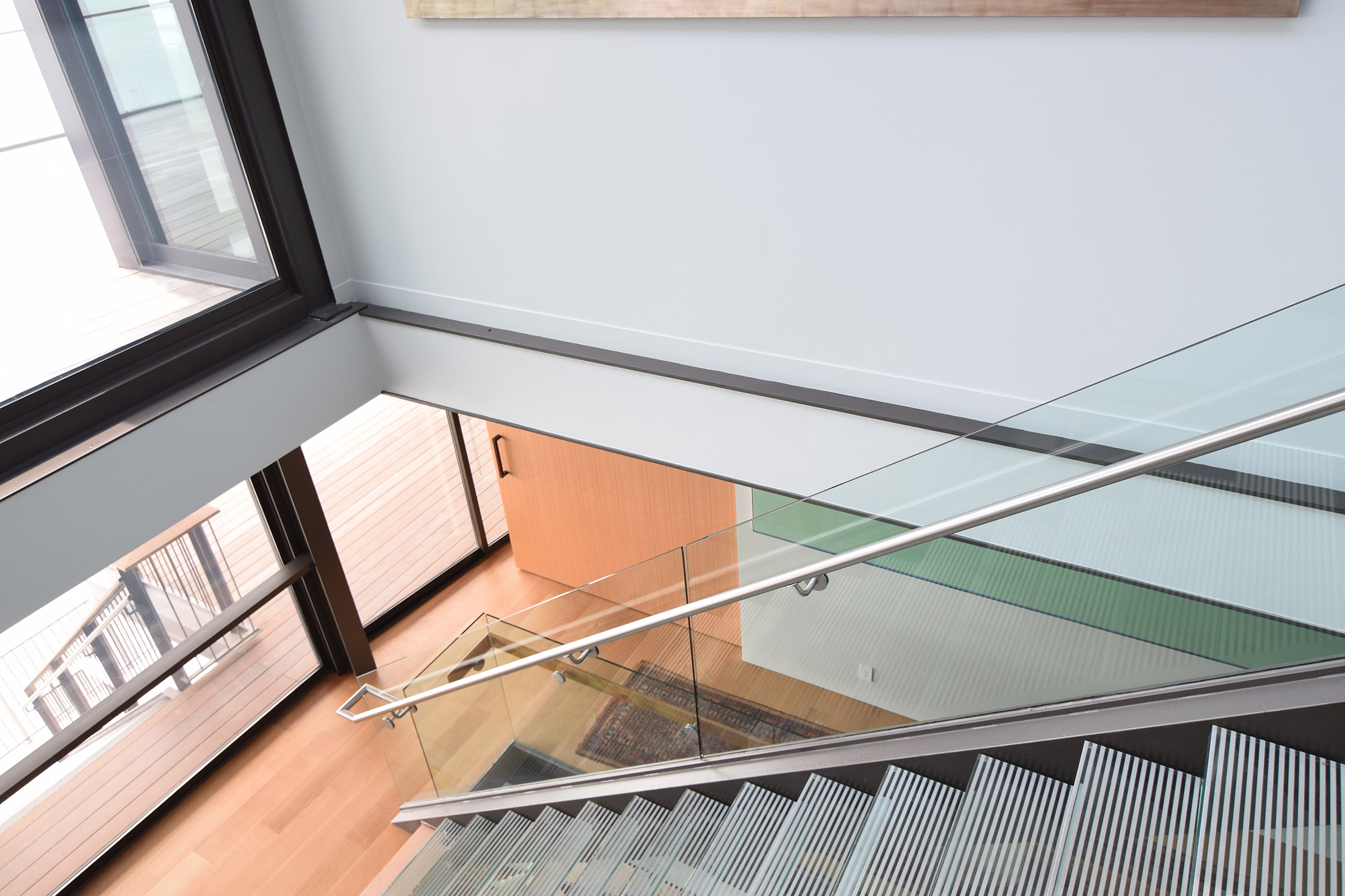 Staircase view to custom Rift Anigre Pocket Door, closed