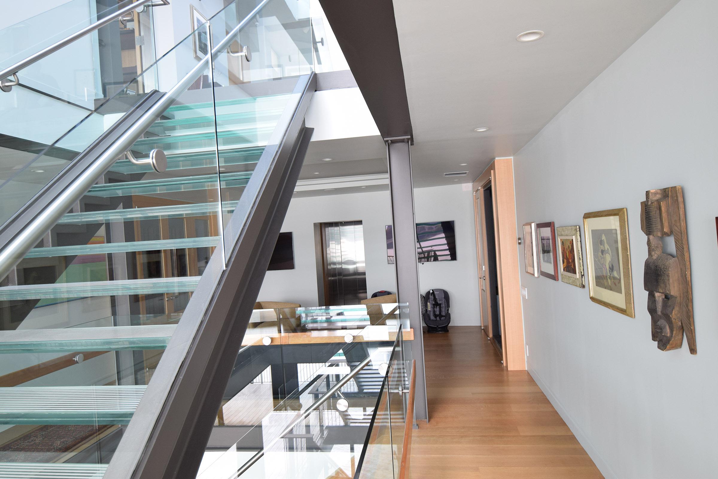Staircase view to custom Rift Anigre Elevator & two Rift Anigre Wine Closets with Walnut Interiors