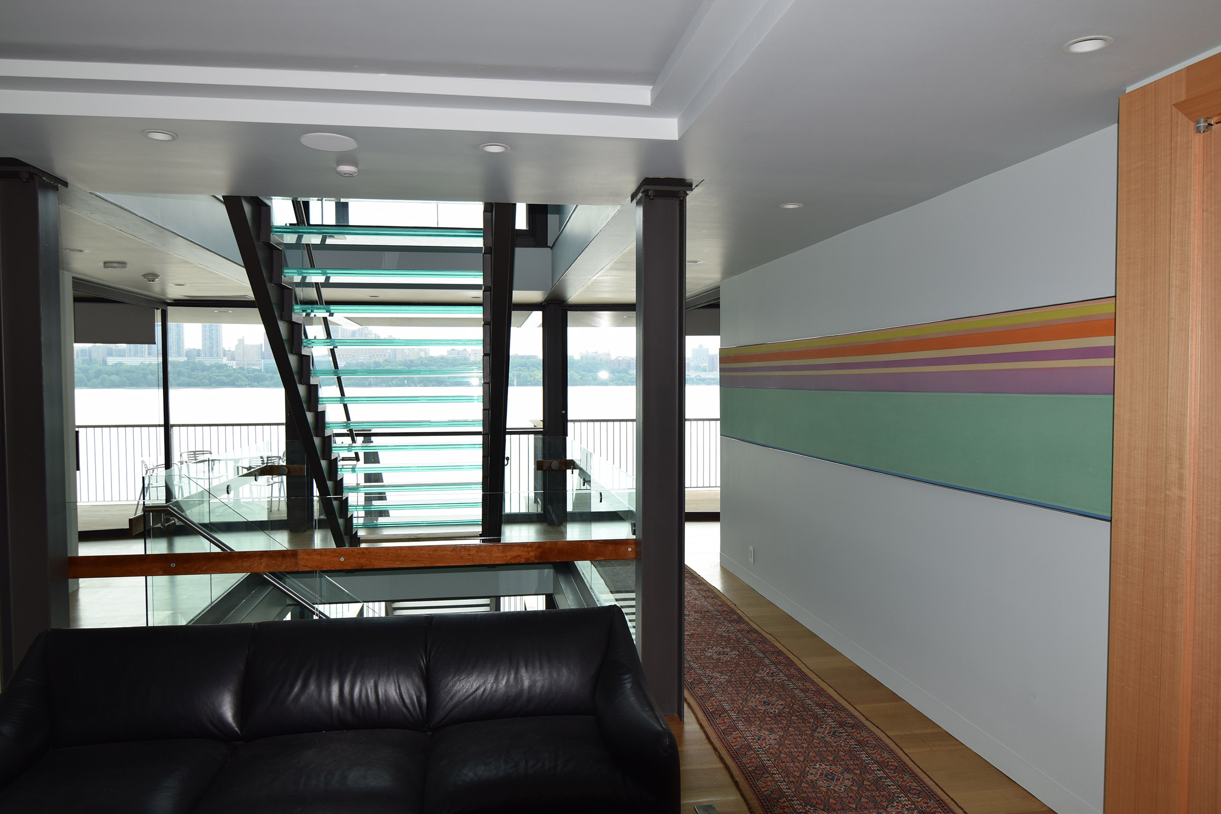 Staircase view including edge of Rift Anigre Wine Closet & open Pocket Door