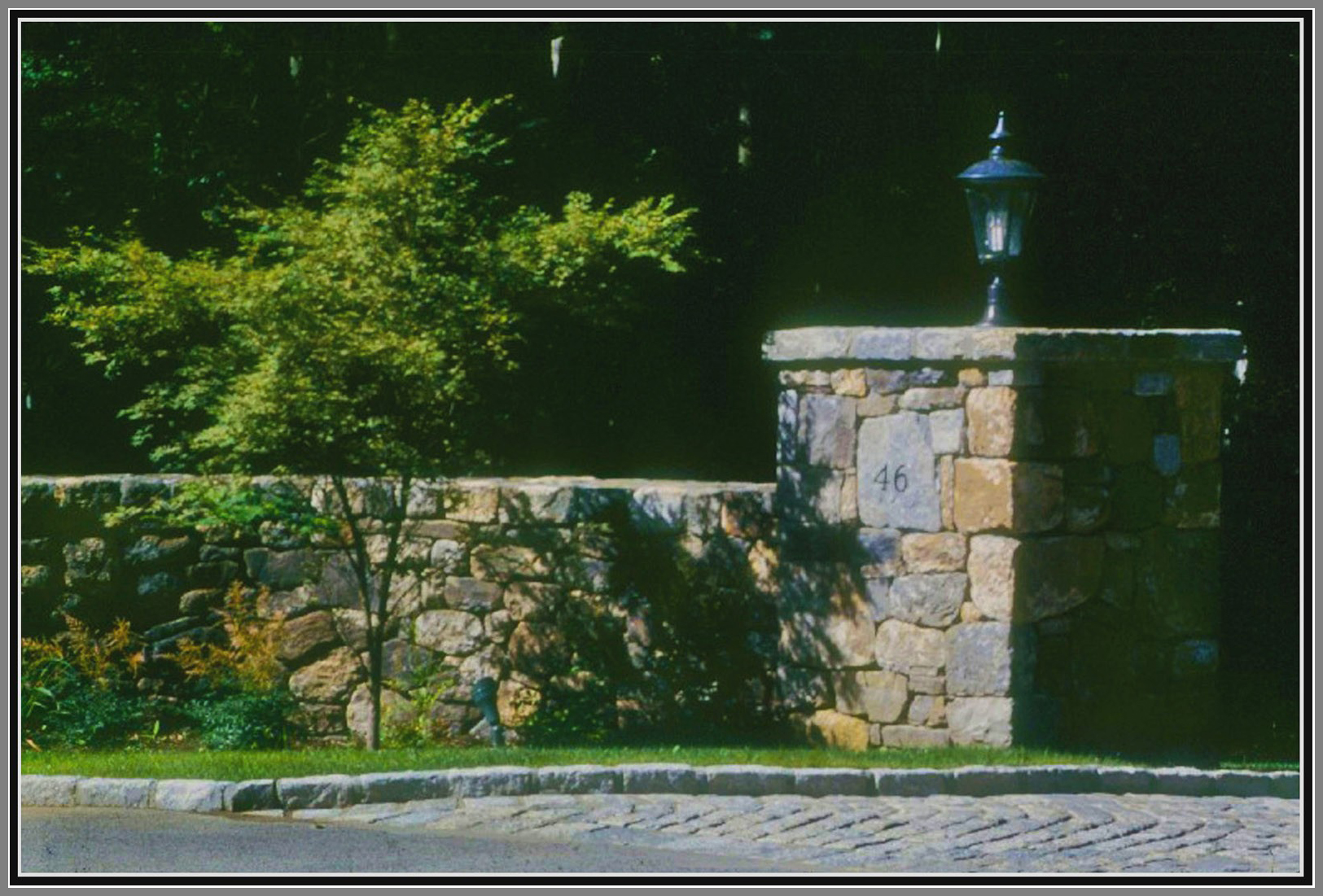 Field stone columns and wall with cobblestone apron and curb