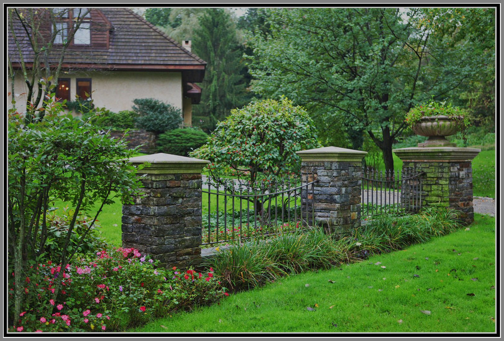 Wrought iron fence with stone column by Artistic Outdoors